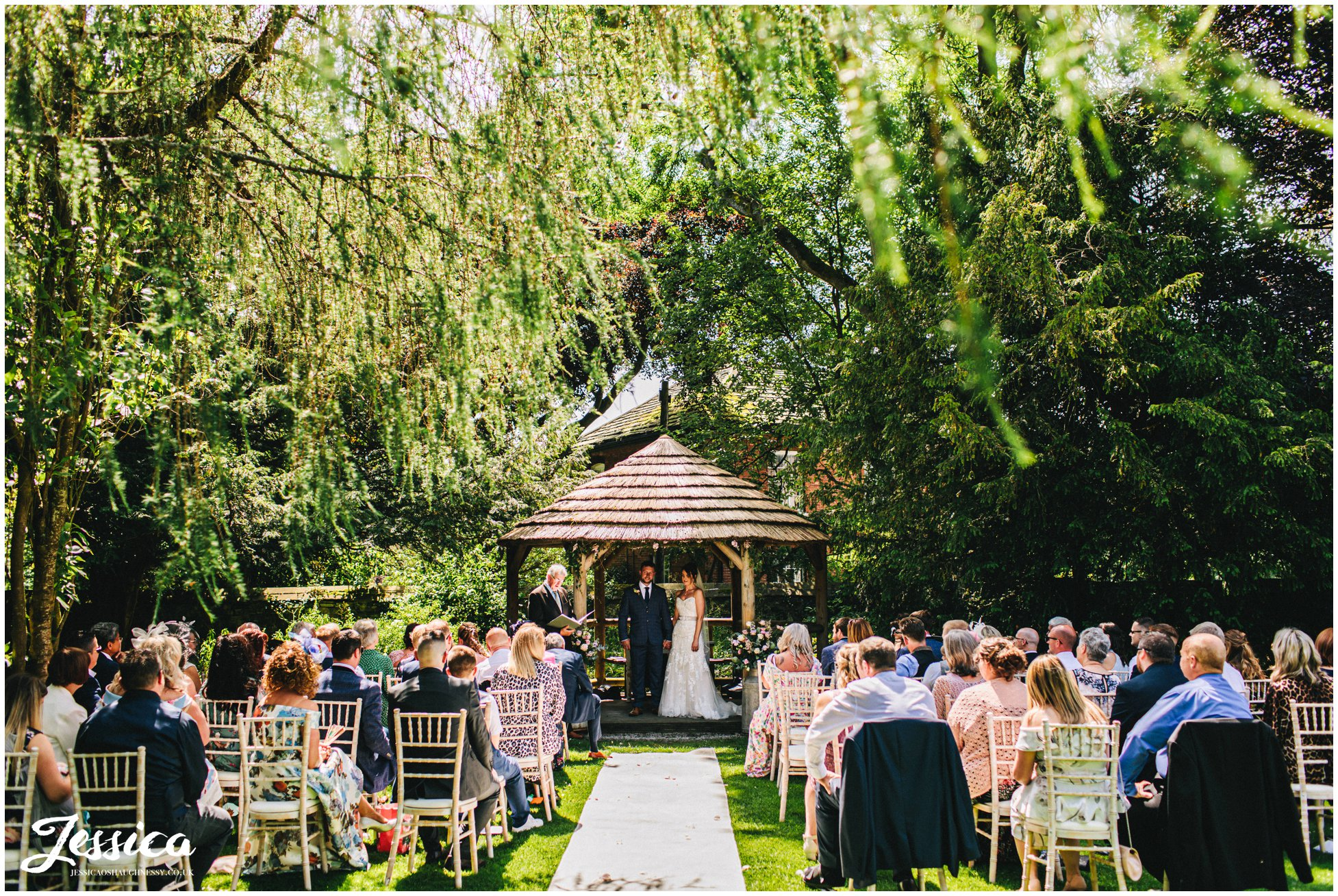 bride & groom stand under floral structure for their outdoor wedding at eyam hall in derbyshire