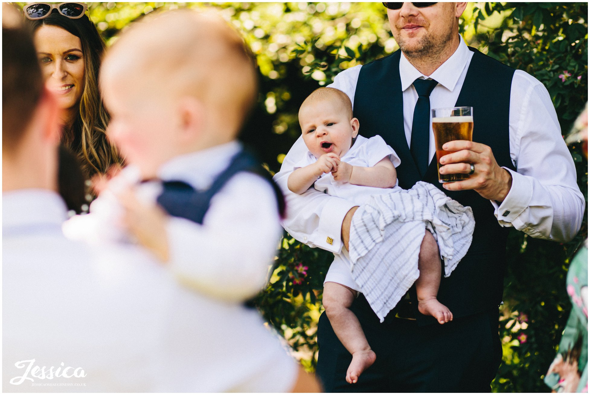 guest holds baby & beer during the festivities