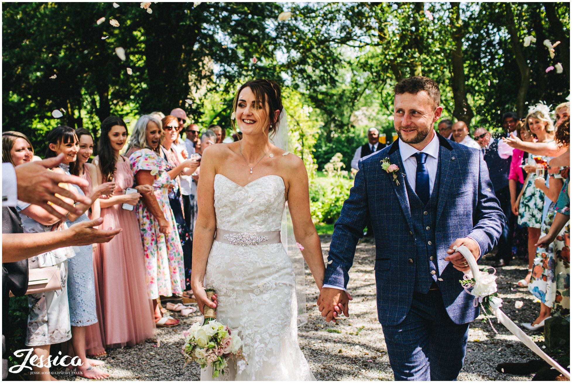 the couple are showered in confetti at eyam hall in derbyshire
