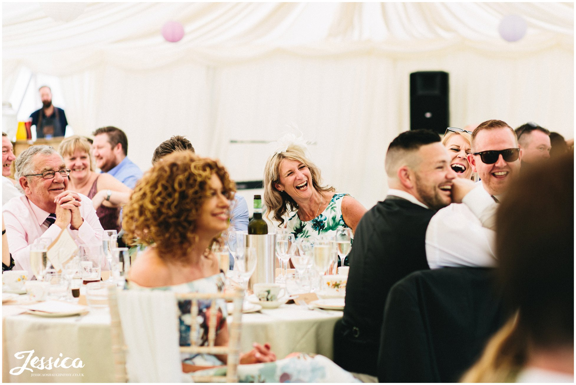 wedding guests laugh as the speeches are made at eyam hall in derbyshire