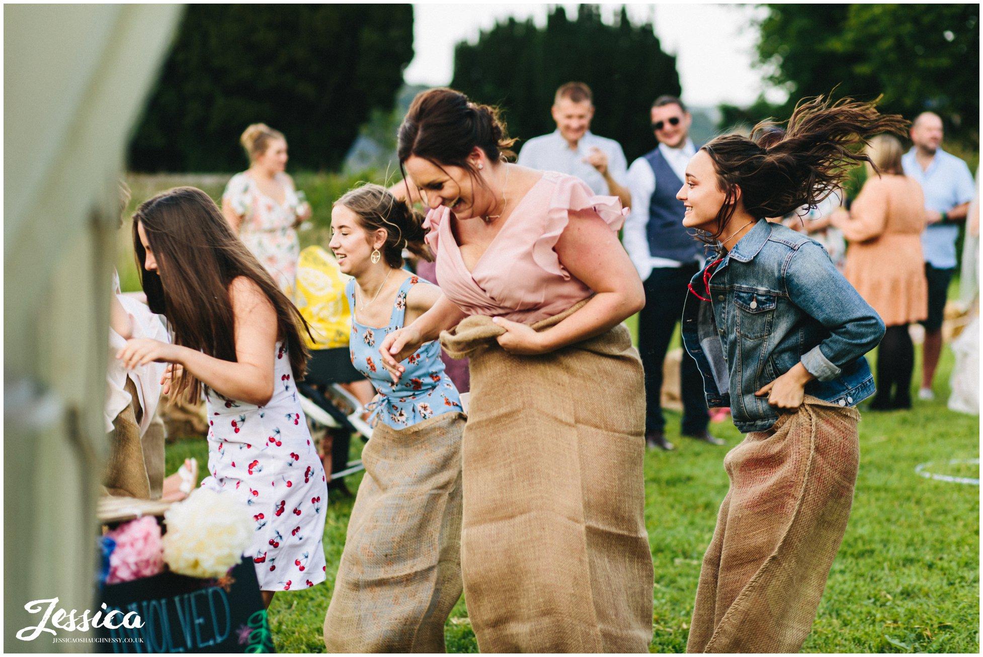 wedding guests enjoy a sack race in eyam hall gardens