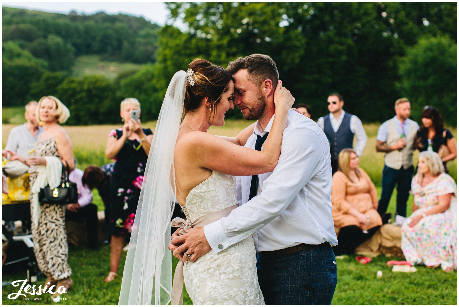 bride & groom have first dance outside surrounded by guests
