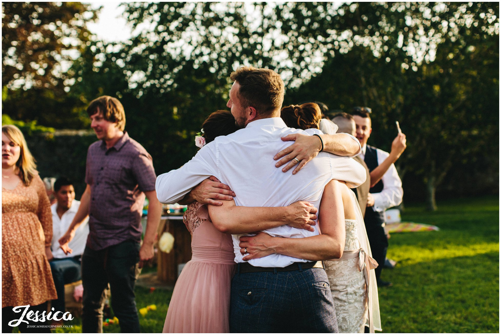 guests have group hug after the first dance ends