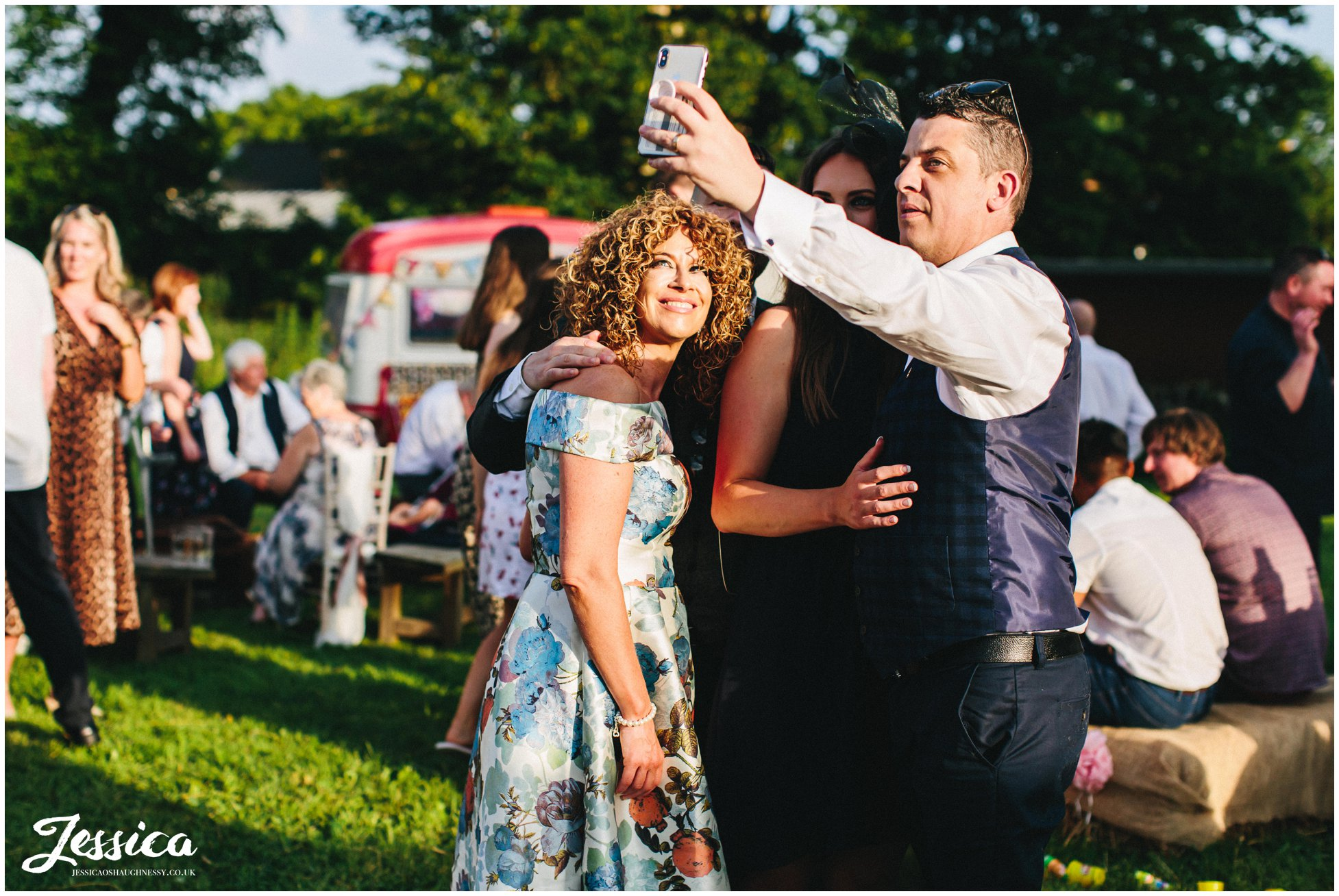 wedding guests take selfie in the evening sun