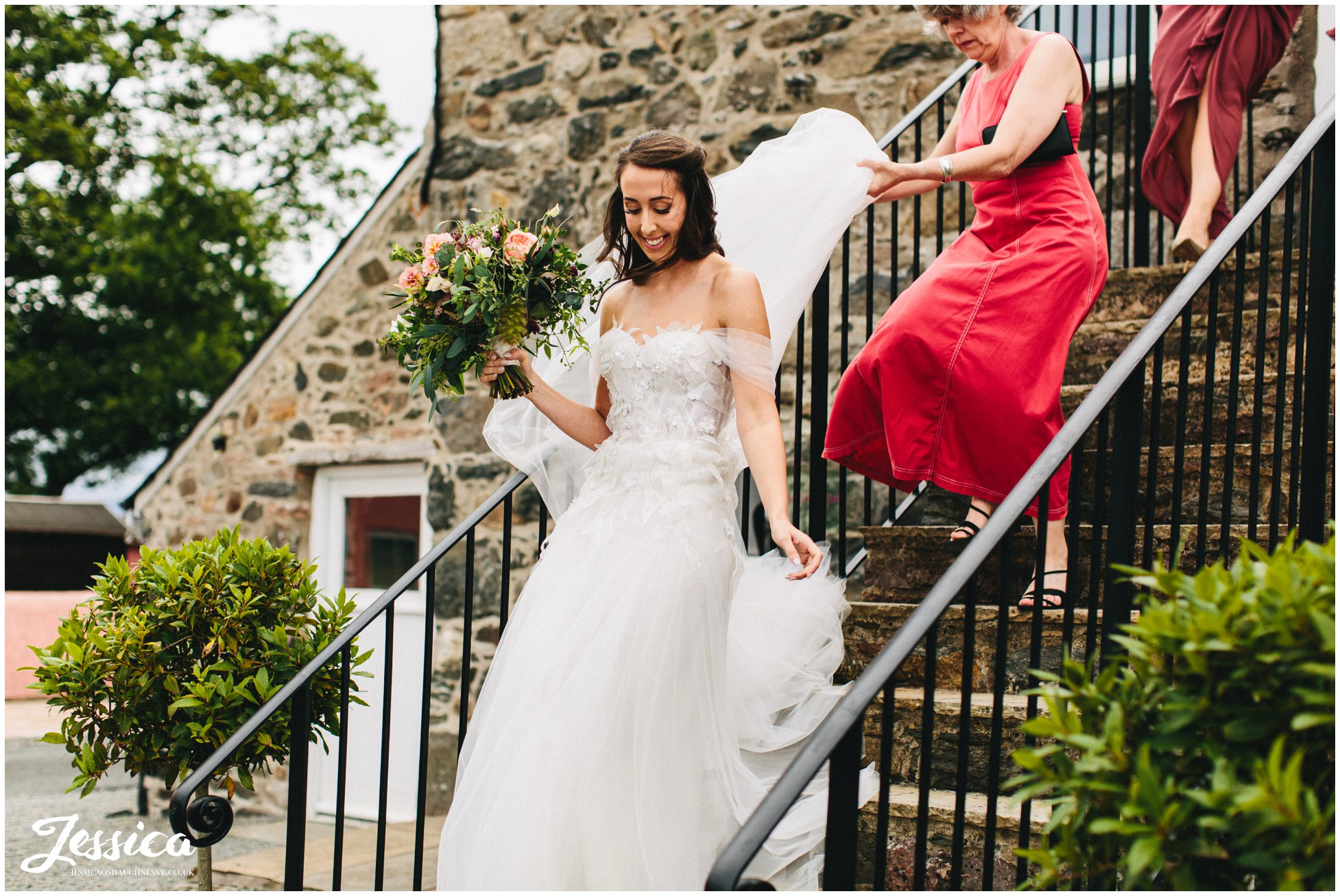the bride walks down the barn stairs to the ceremony