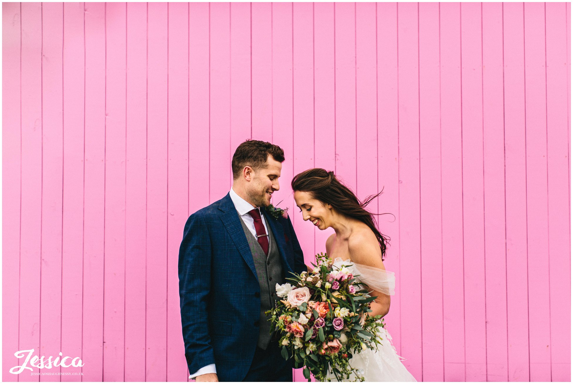 the bride & groom stand in front of the pink shepherds hut colourful wedding photography