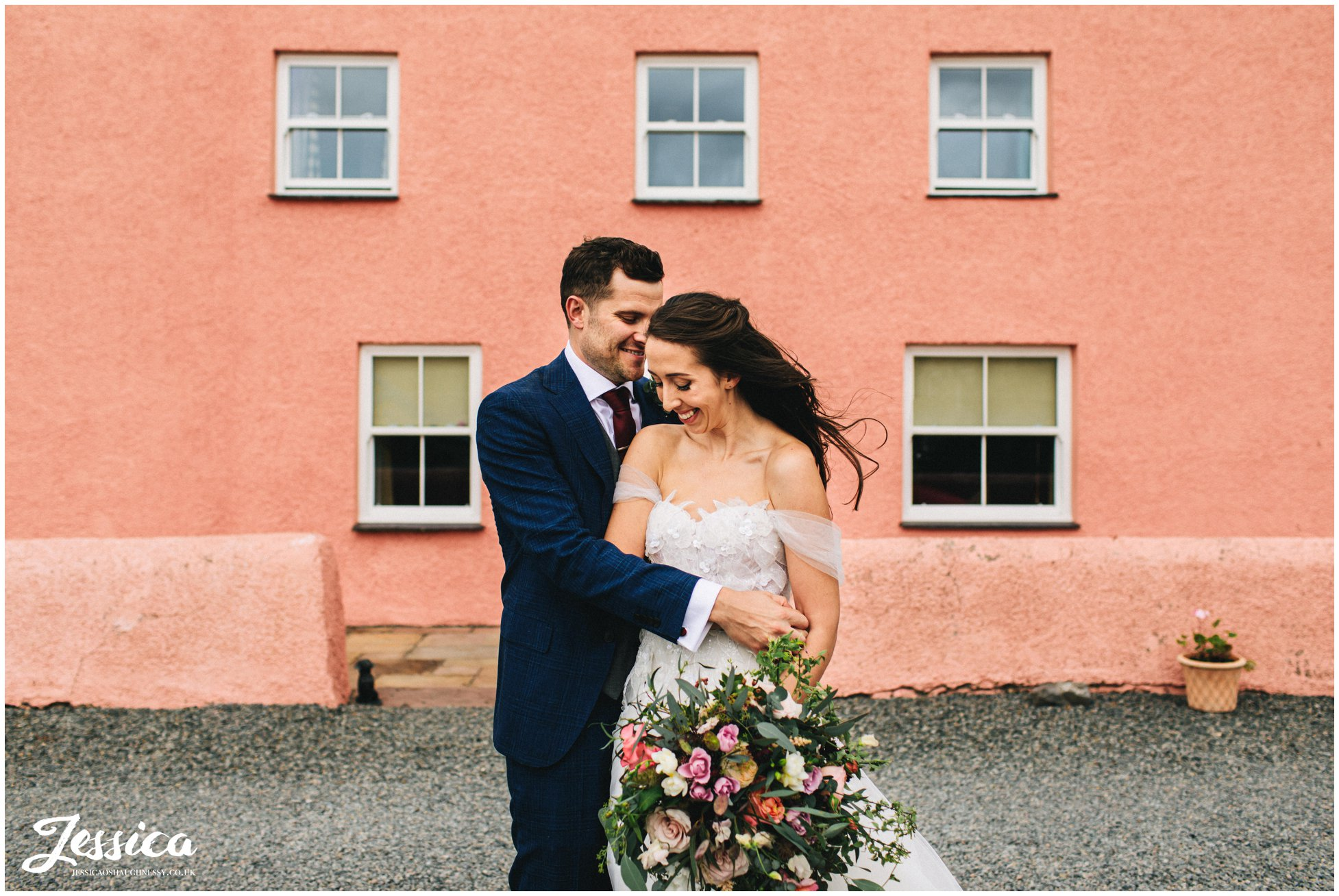 newly wed's have photographs in front of the pink farm house in anglesey