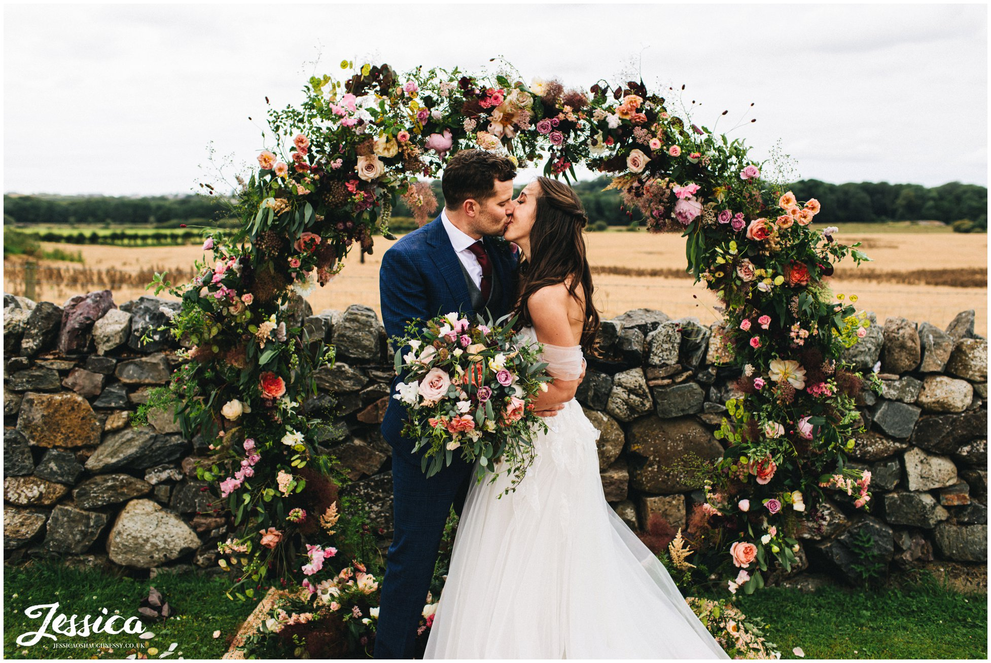 bride & groom kiss in front of floral arch