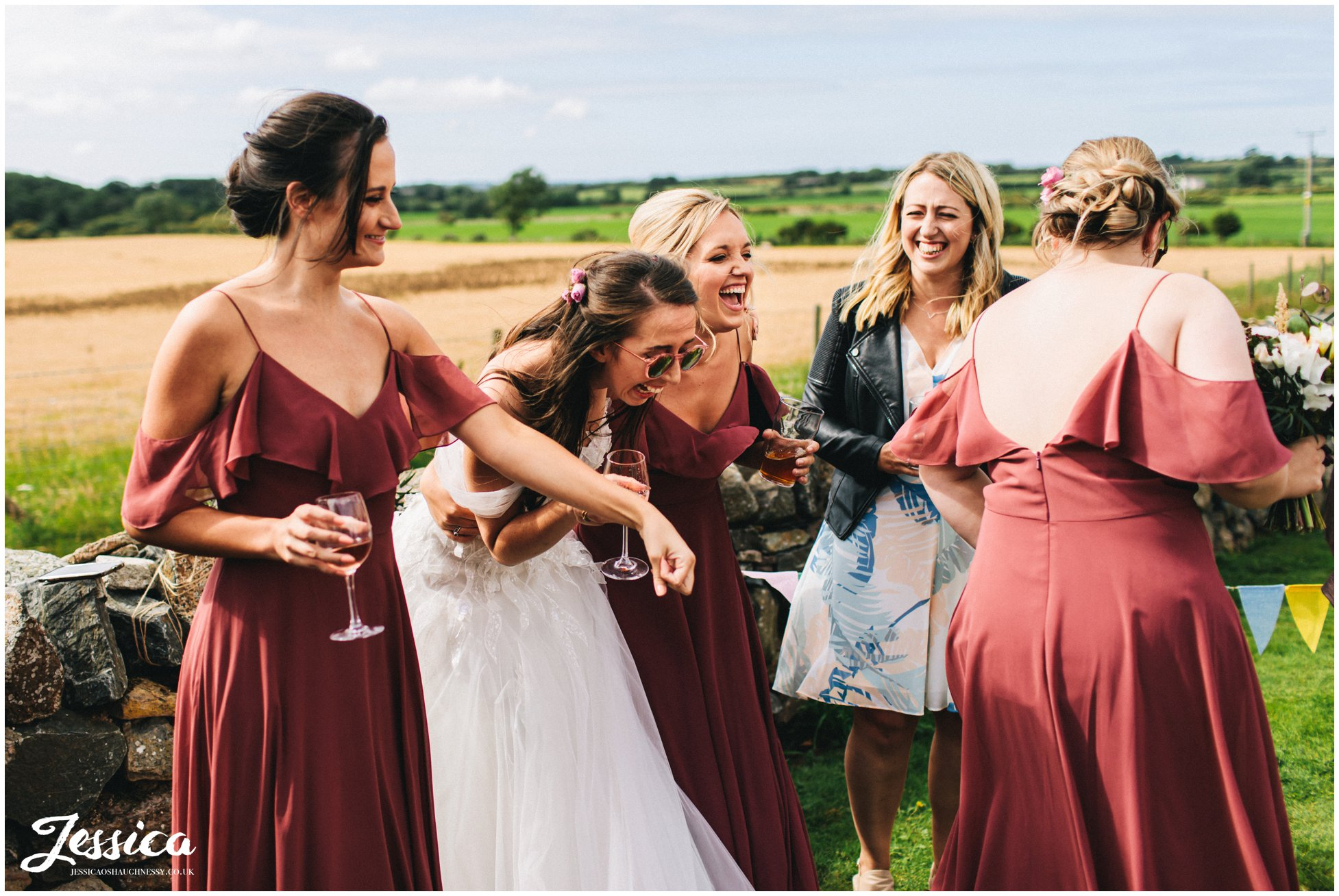 bride laughs with her bridesmaids during the reception