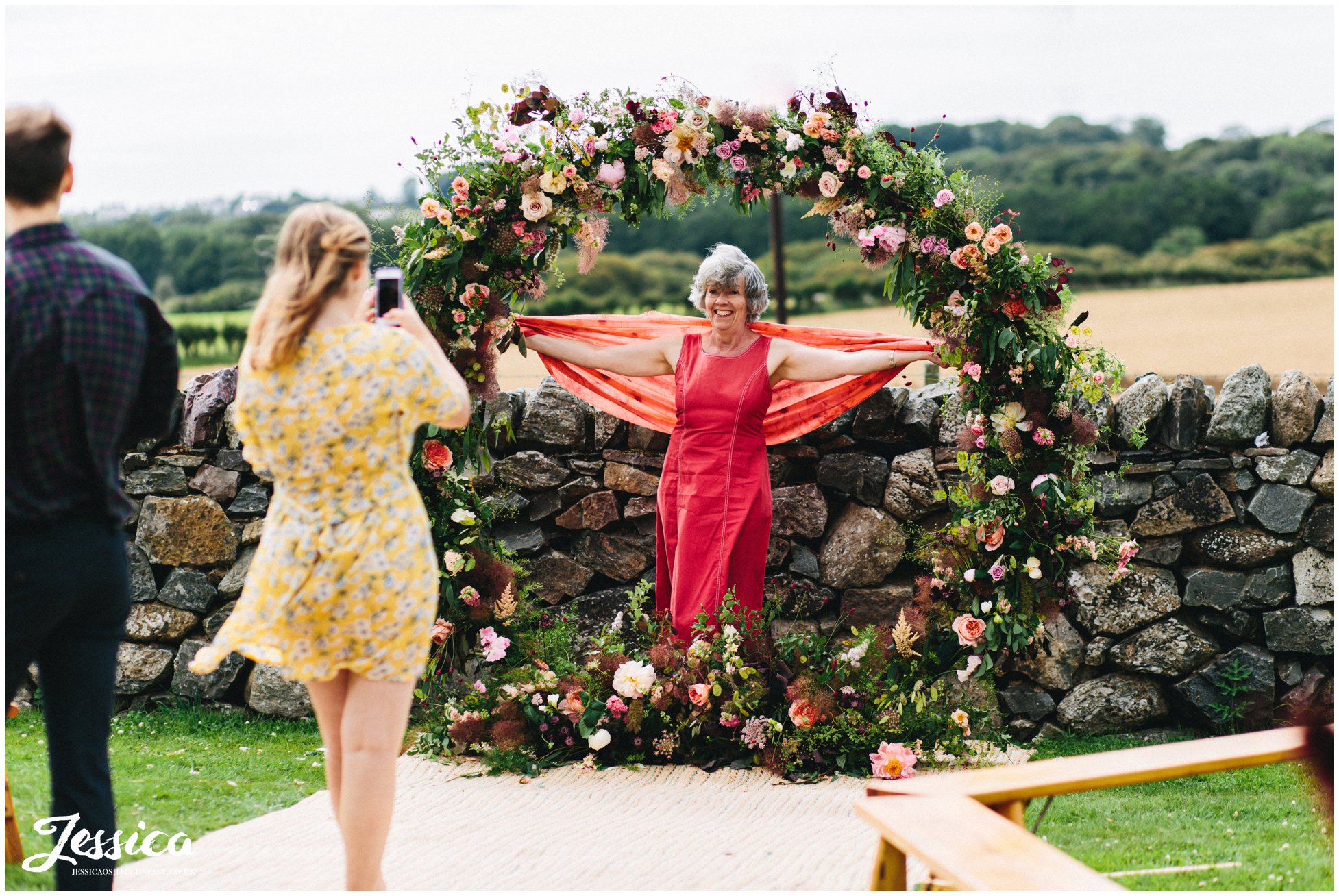 guests pose with the floral arch at the outbuildings, anglesey
