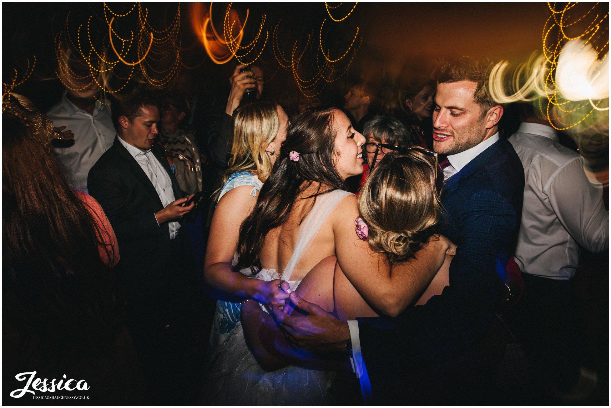 couple group hug their friends on the dance floor