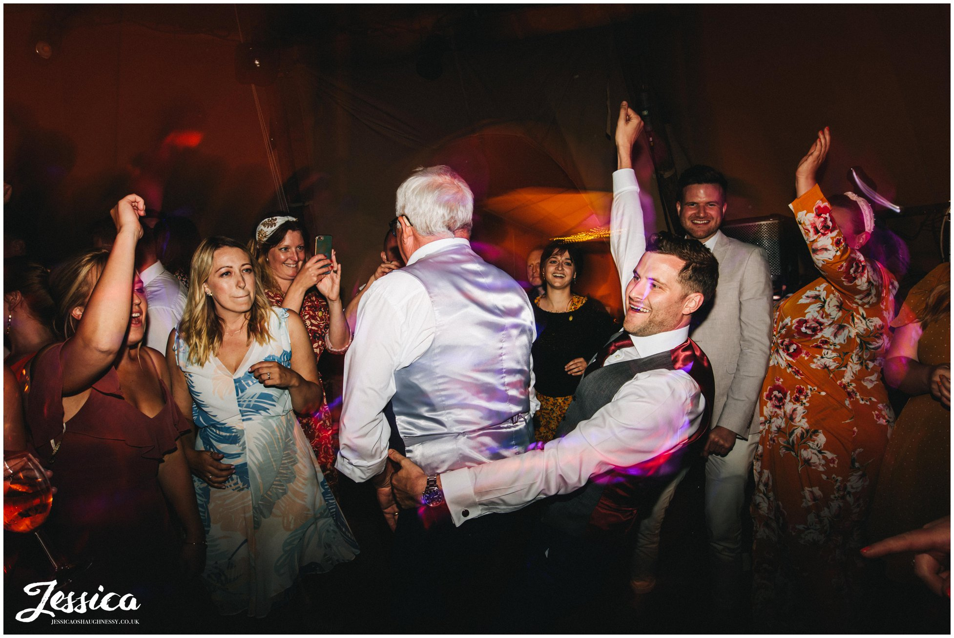groom dances with dad in the tipi