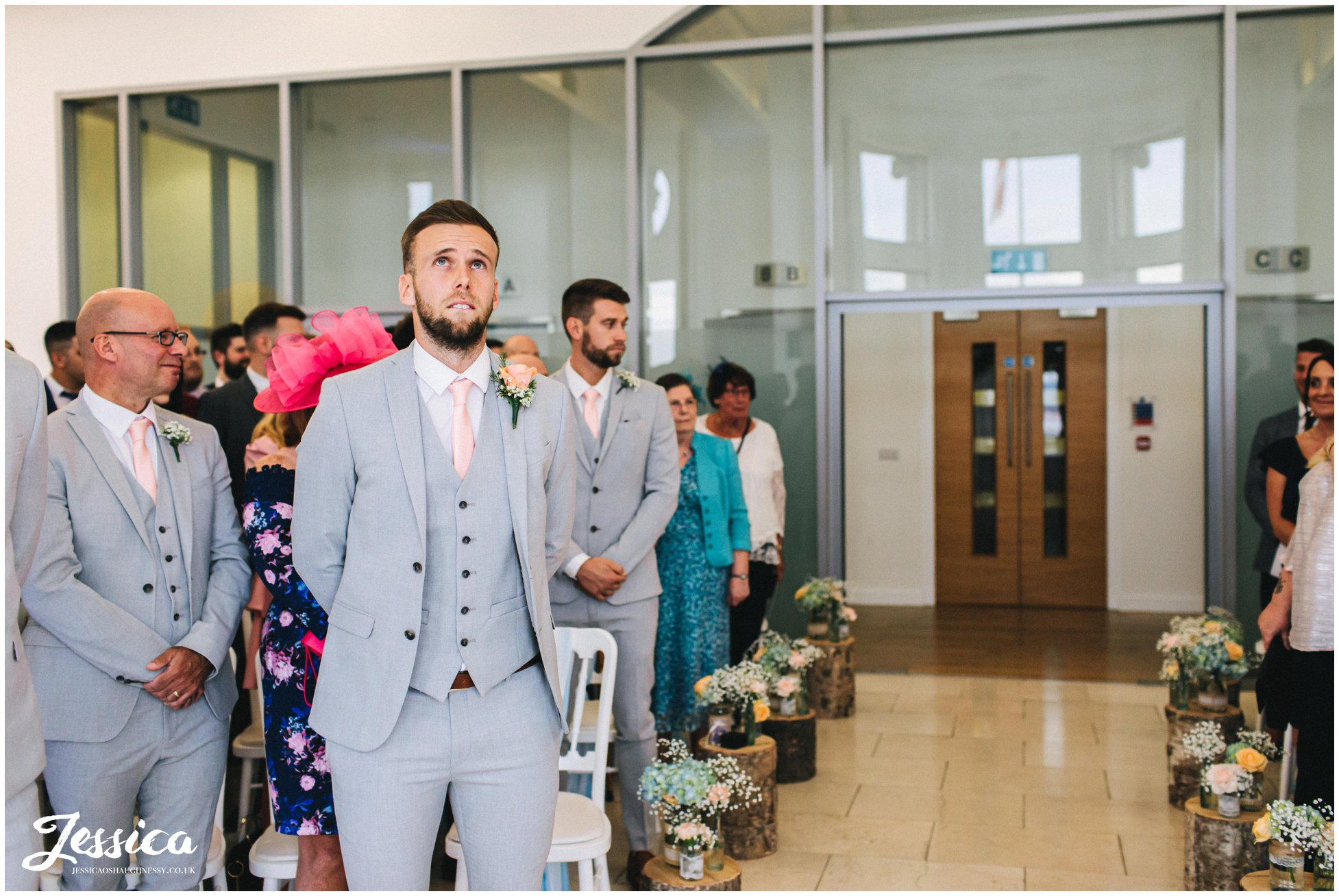 the groom looks emotional as he waits for his bride