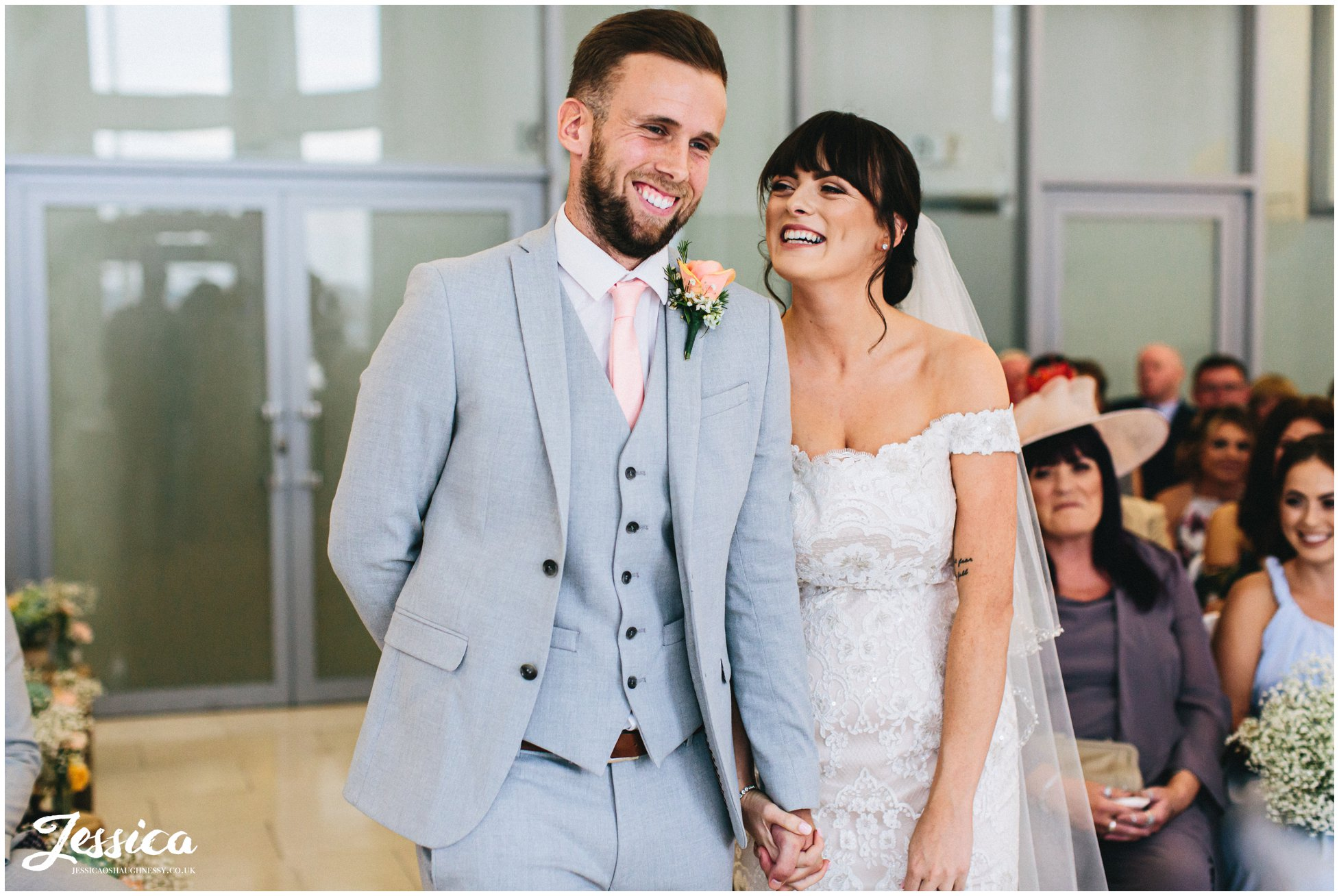 the couple laugh together during their liverpool wedding