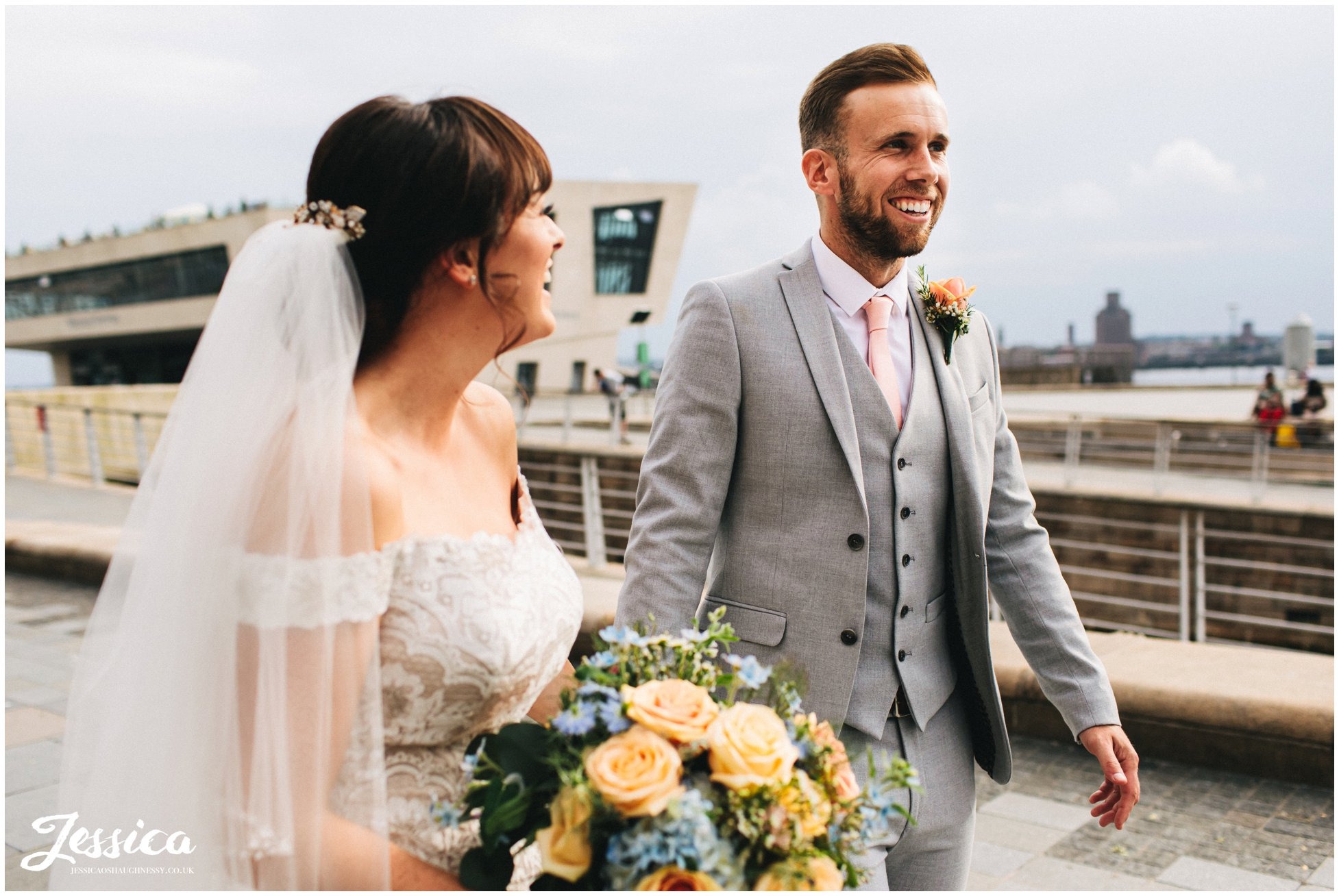 bride laughs at groom as they walk together