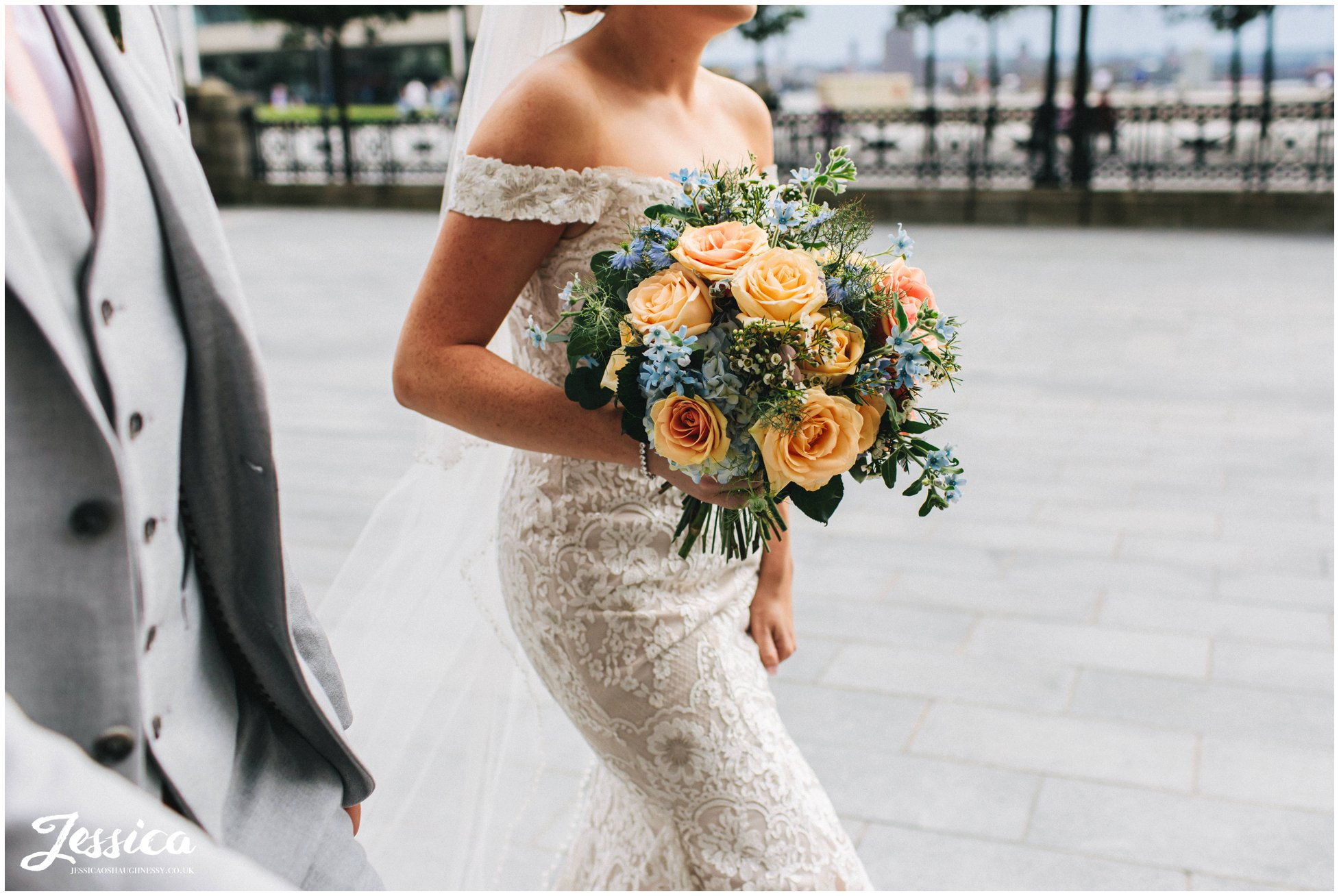 the bride carries blue & peach bouquet