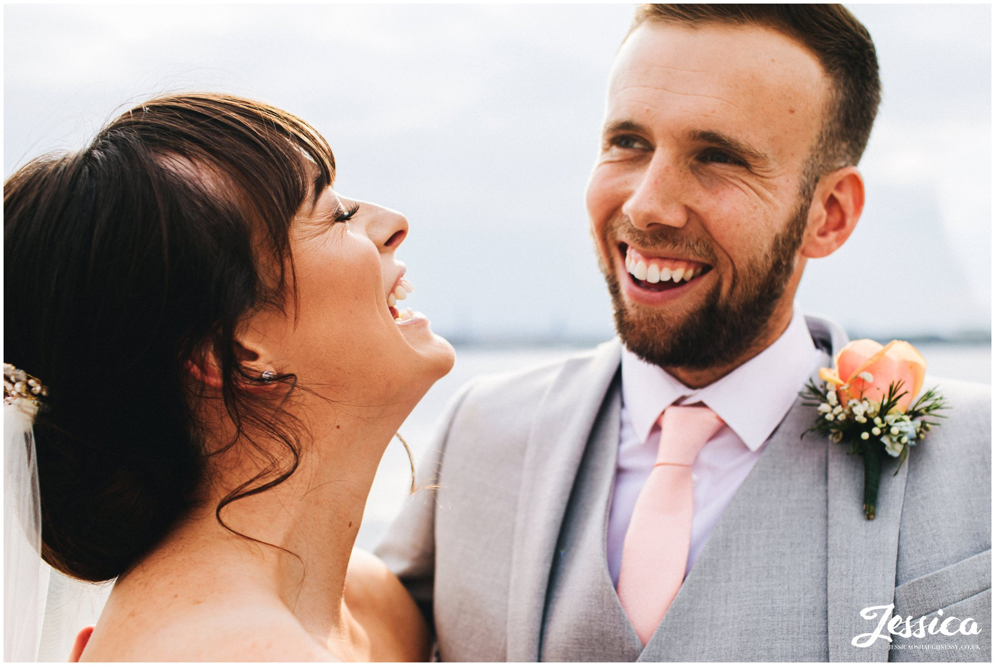 bride & groom laugh with each other on the waterfront