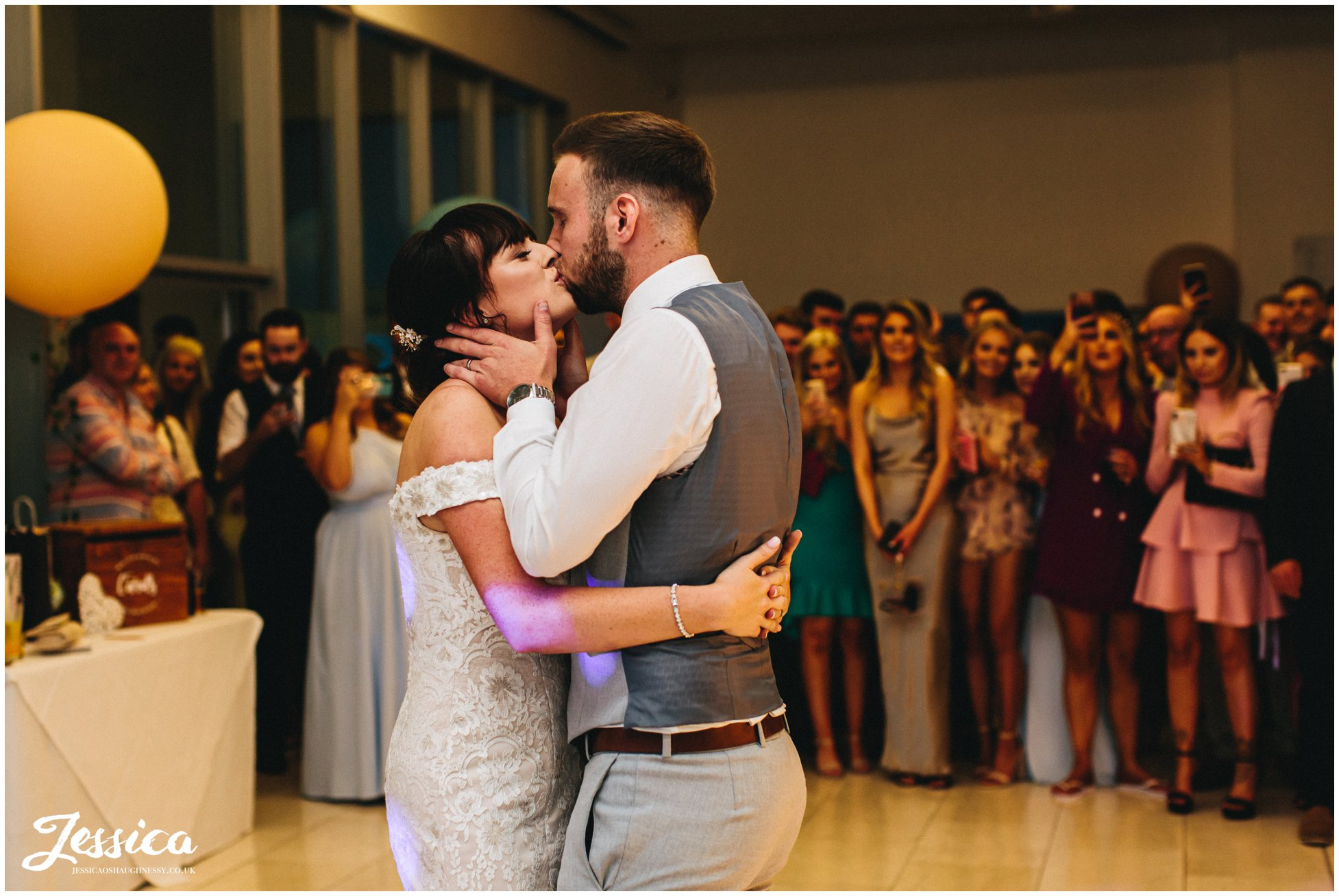 husband and wife kiss during their first dance as a married couple