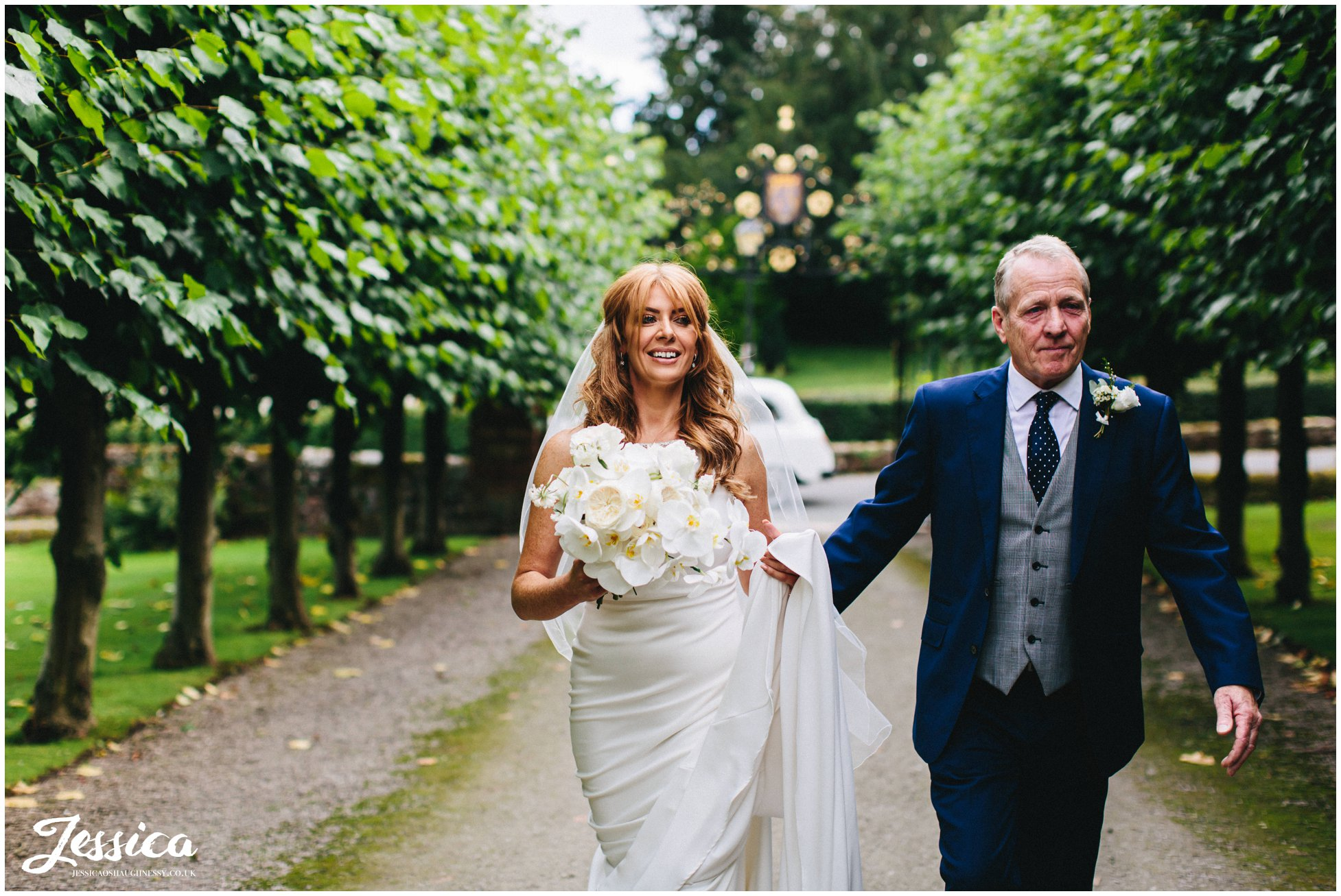 the bride & her father walk down the church path