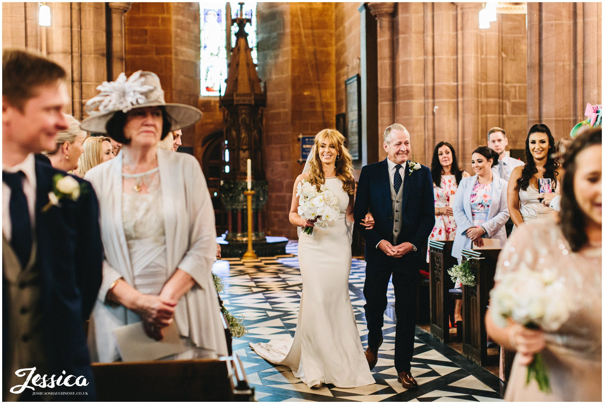 the bride walks down the aisle at eccleston church in chester