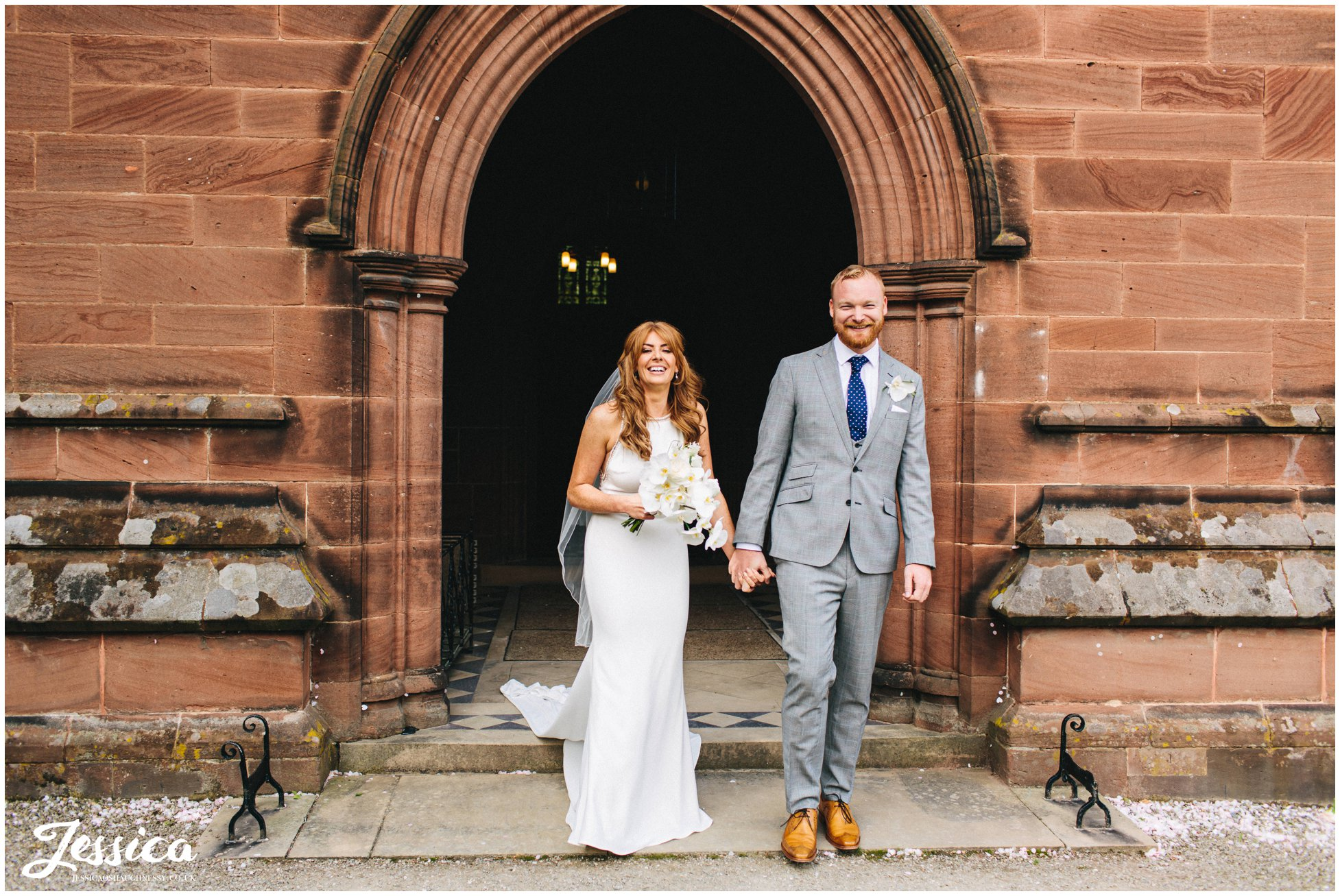 couple smile as they walk out of the church as a married couple