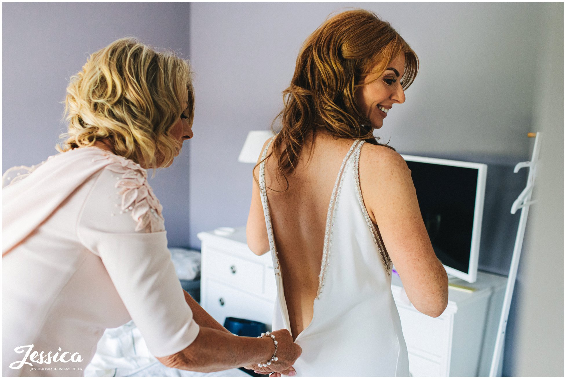 mother of the bride helps daughter into wedding dress