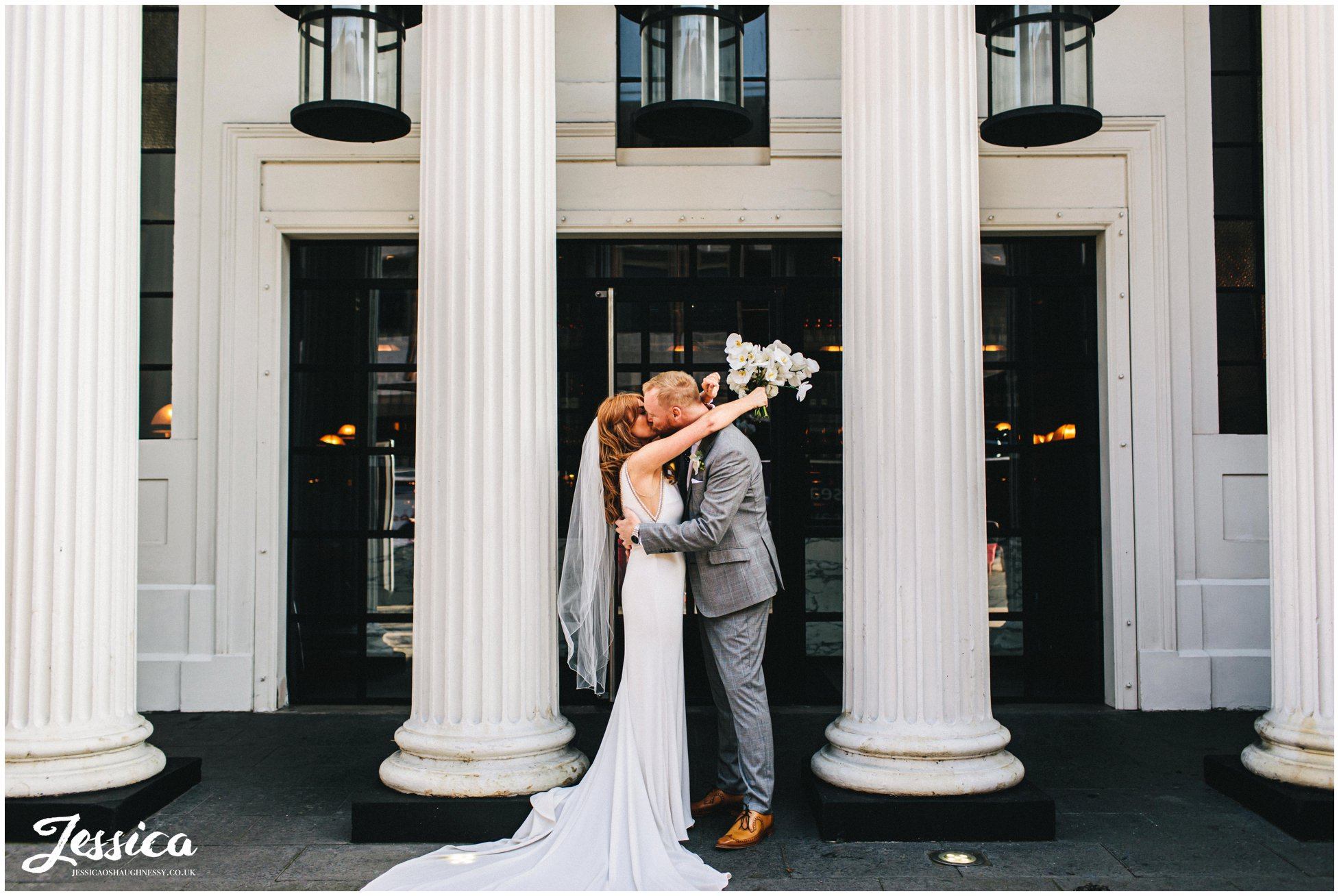 couple kiss in front of the columns at opera grill