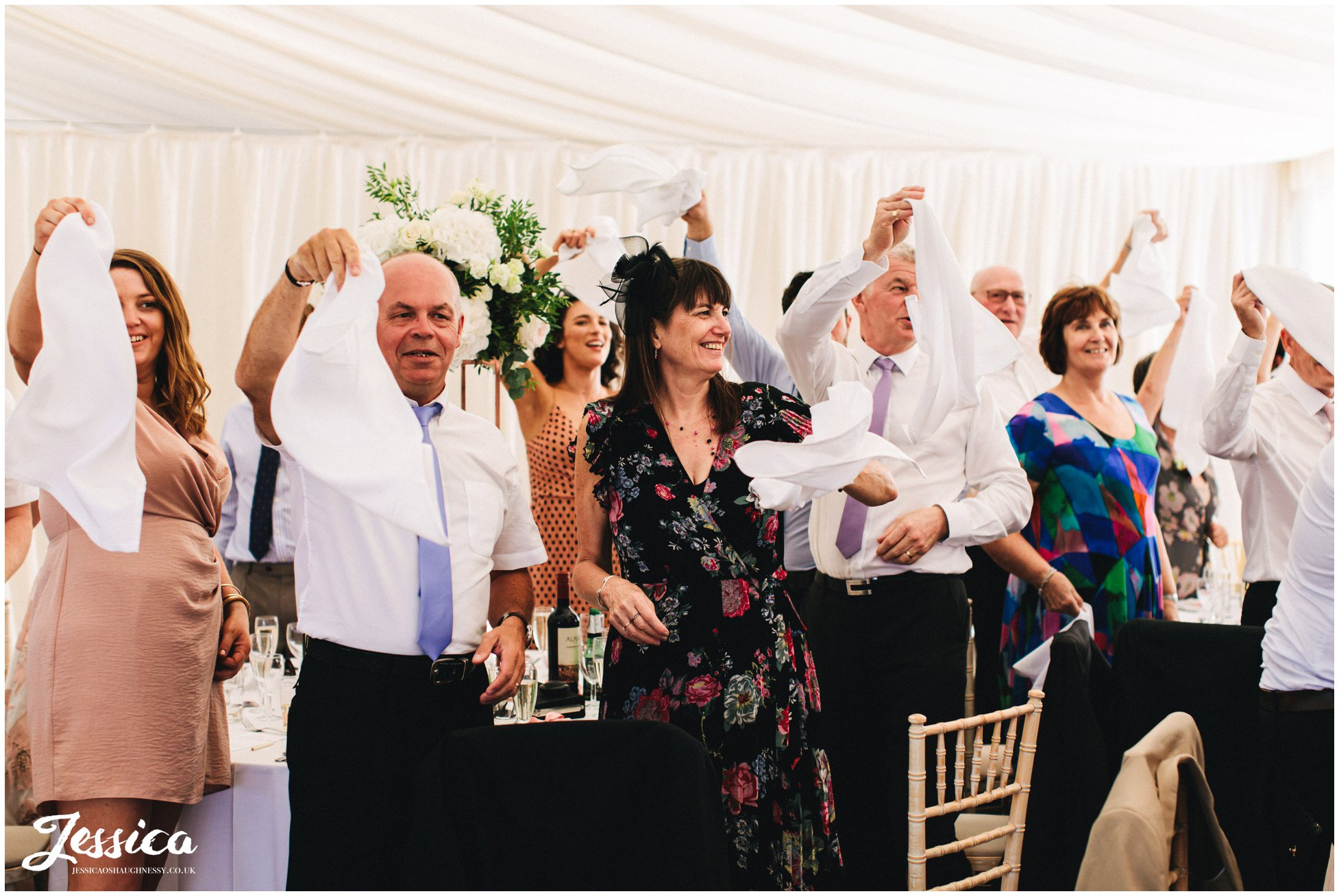 guests wave their napkins as the newly wed's are announced in