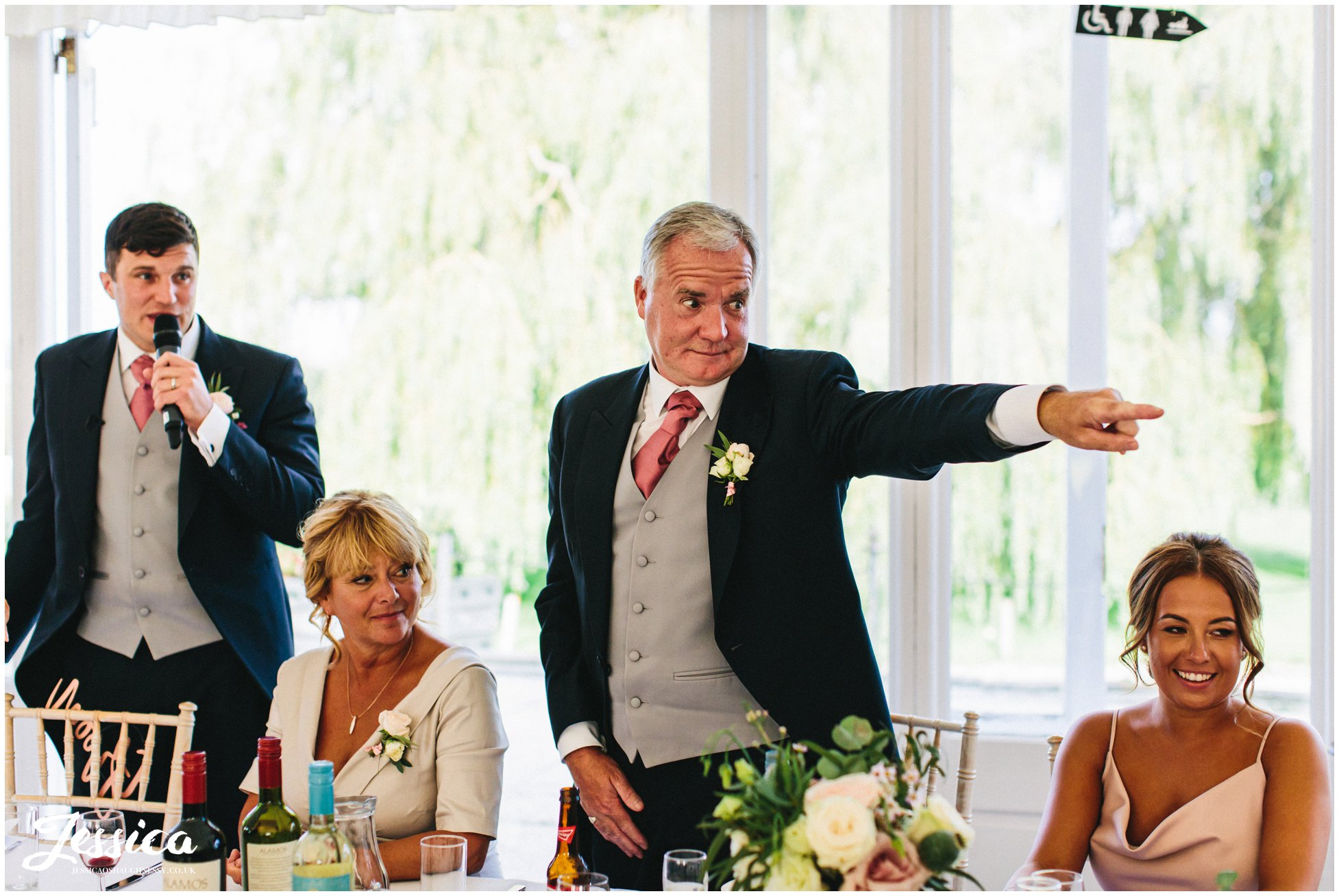 father of the groom points to guests