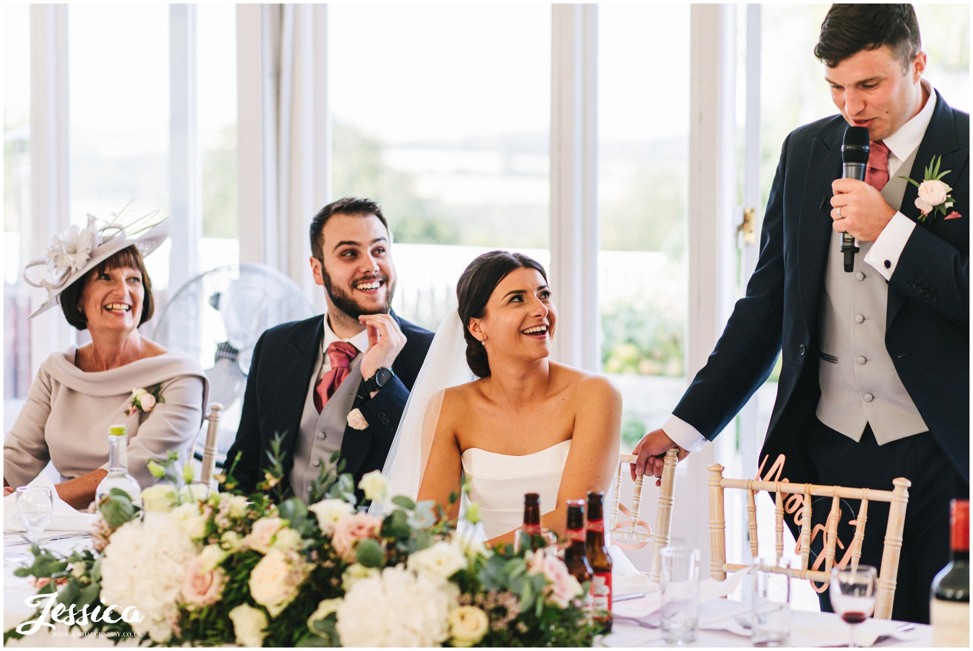 bride laughs as her husband delivers his speech
