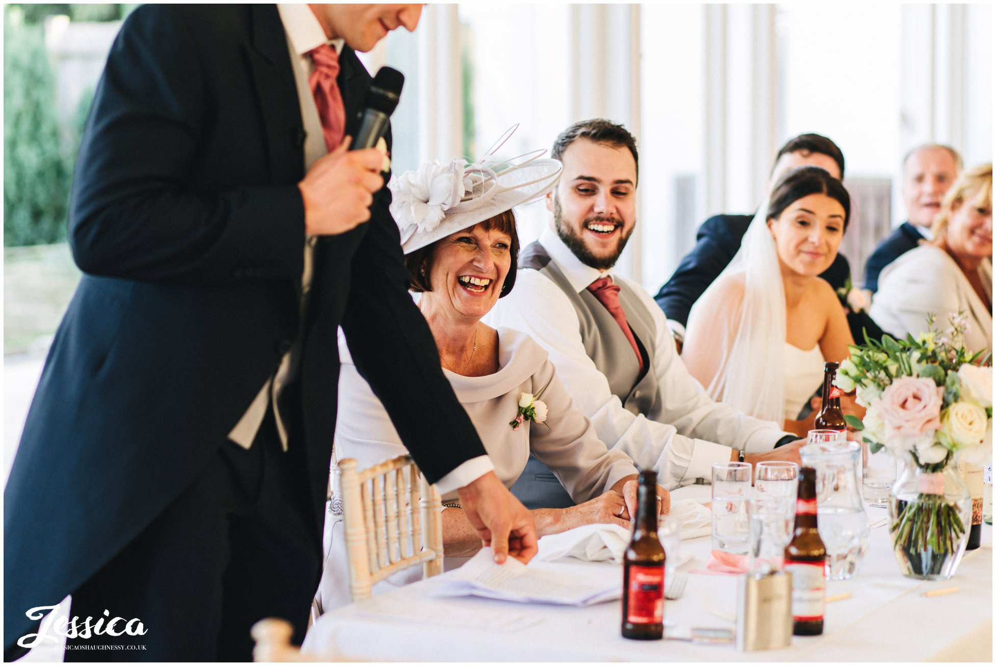 mother of the groom laughs during the best mans speech