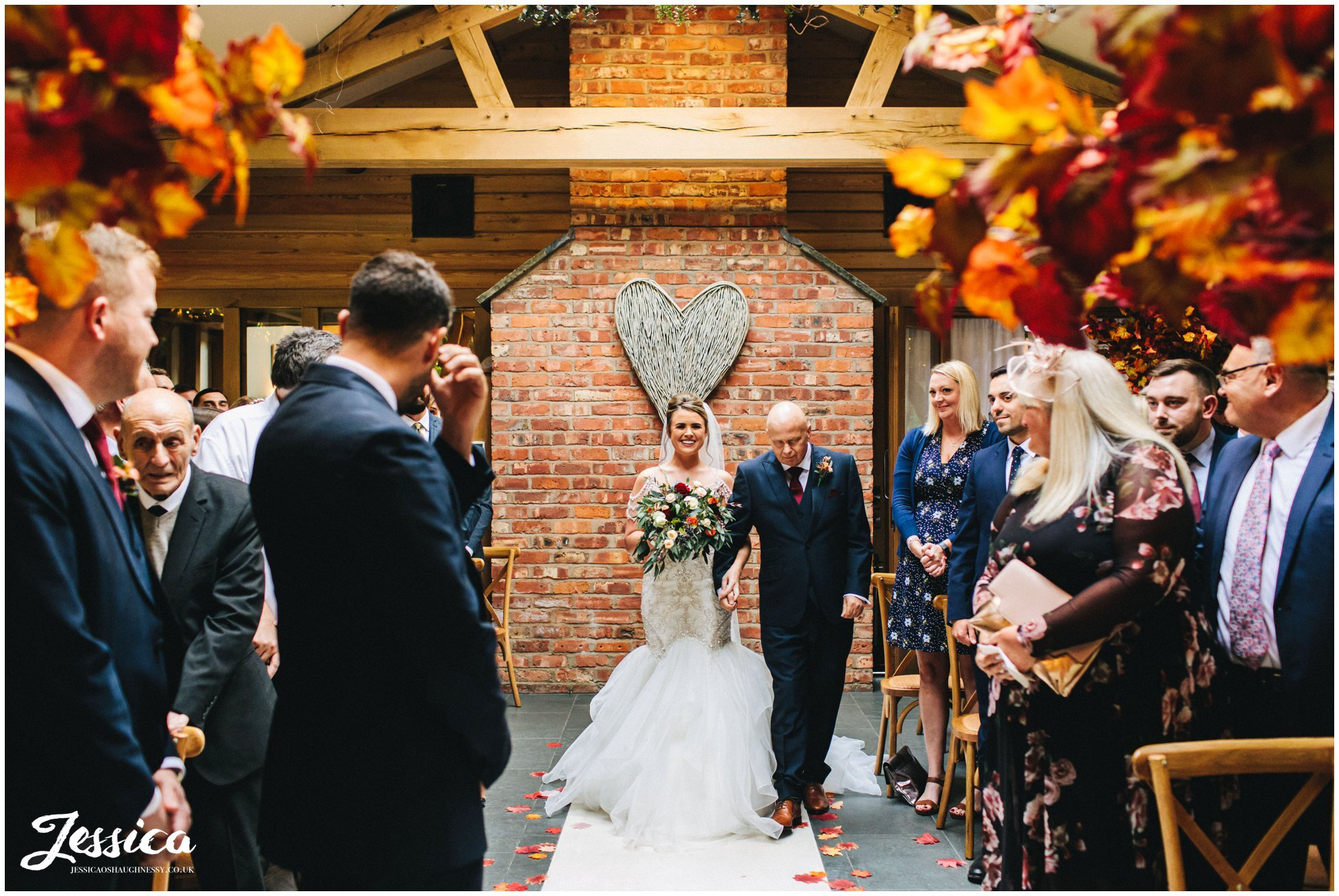 bride walks down the aisle with her father