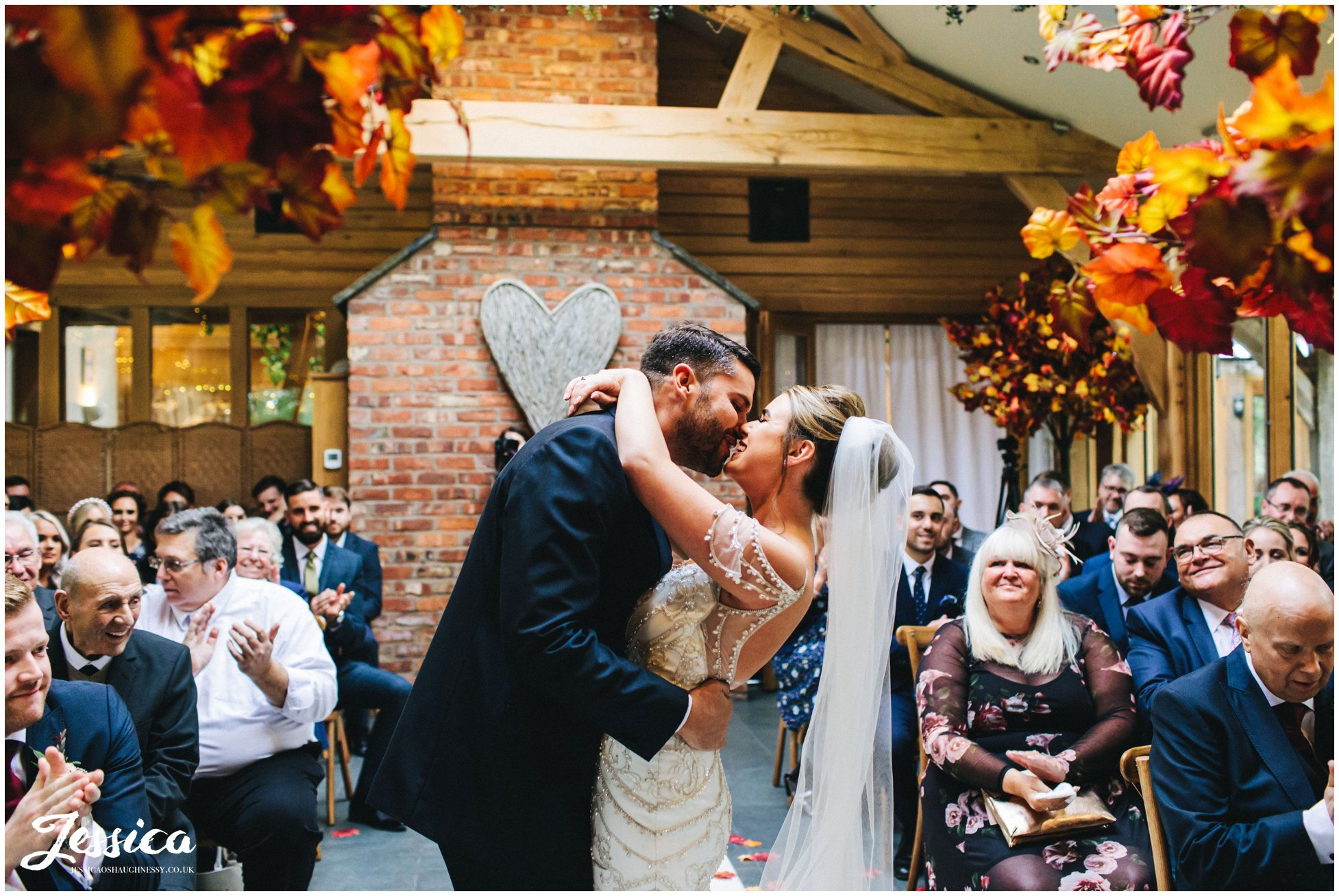 newly wed's share their first kiss at the oak tree of peover