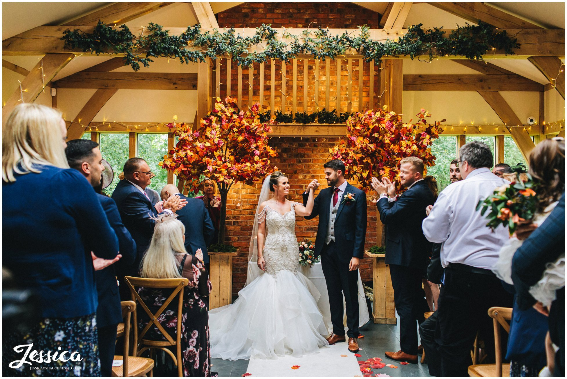 couple walk back down the aisle as husband & wife