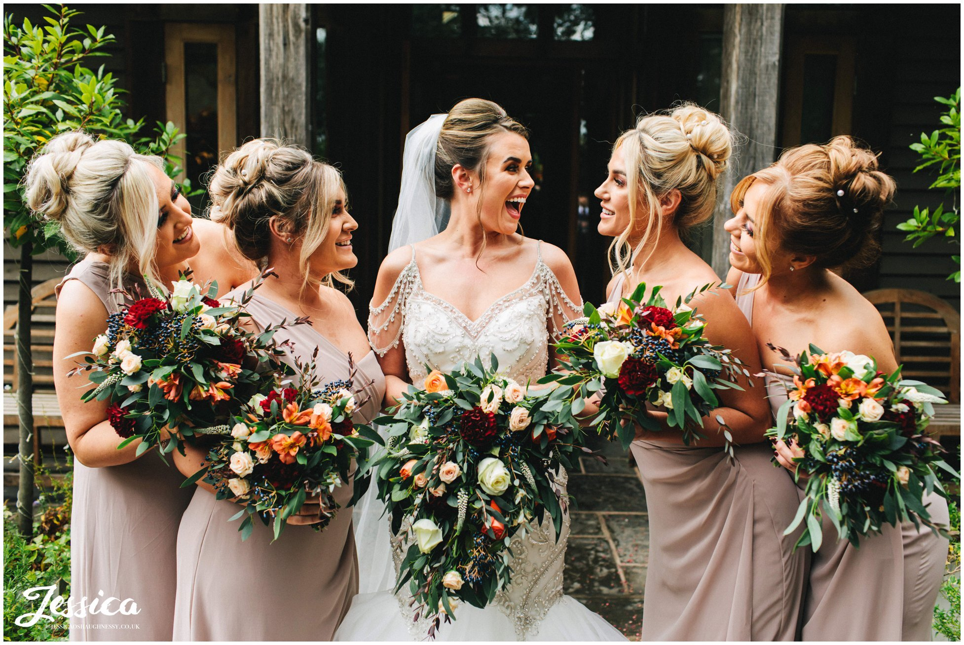 bride laughs with her bridesmaids outside the oak tree of peover