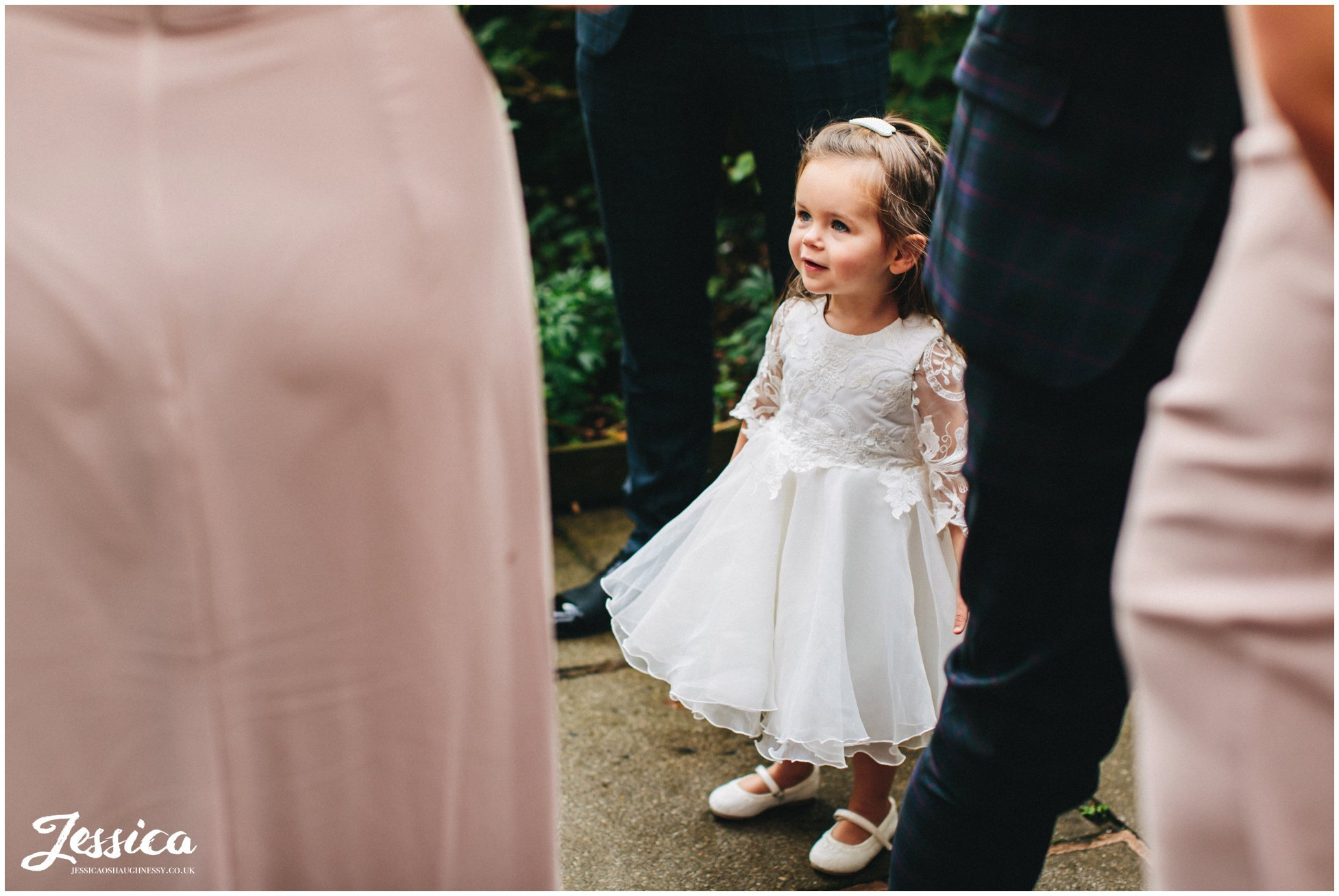 flower girl stands by mum at the oak tree of peover in cheshire