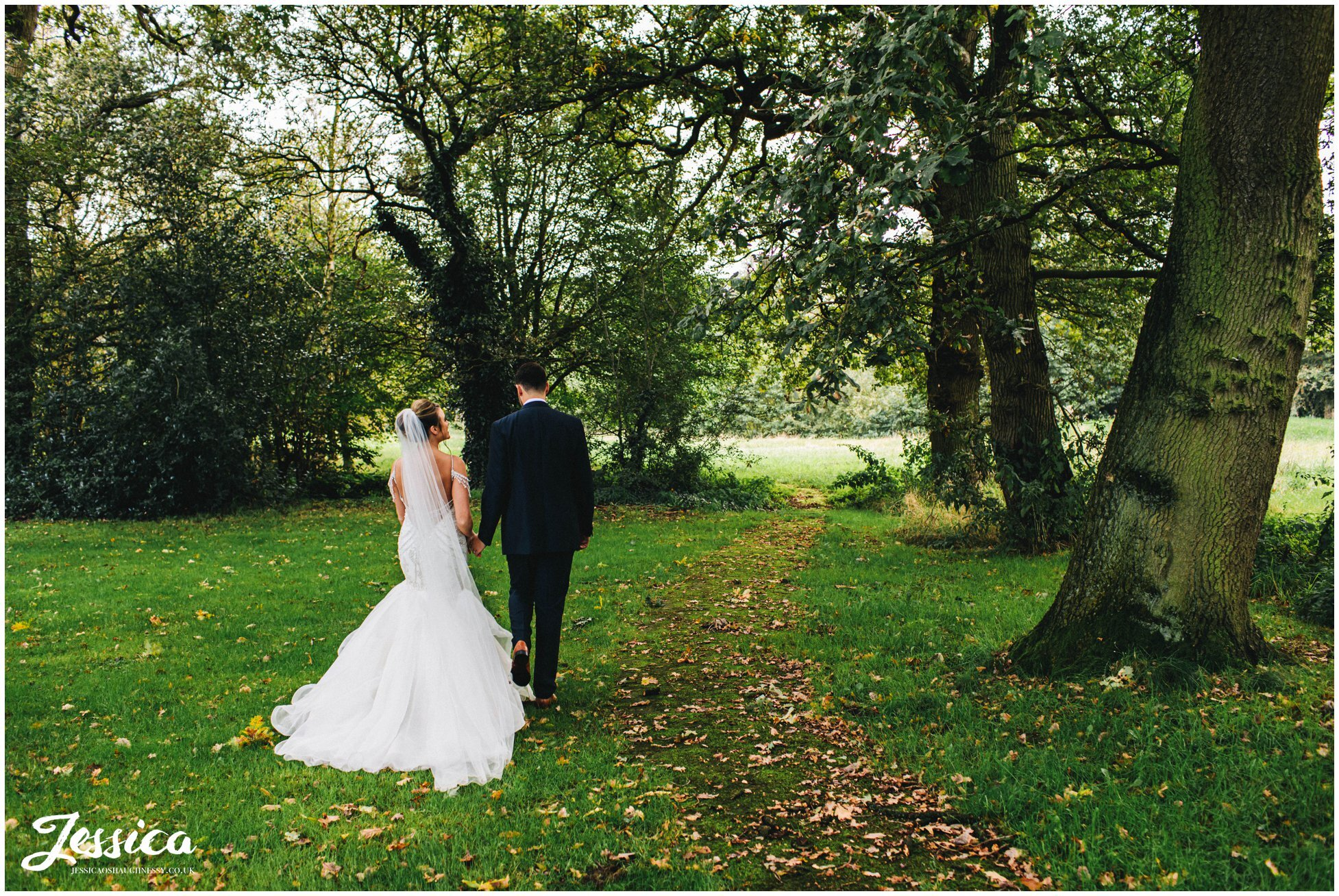 newly wed's walk through the trees in the grounds of their cheshire wedding venue