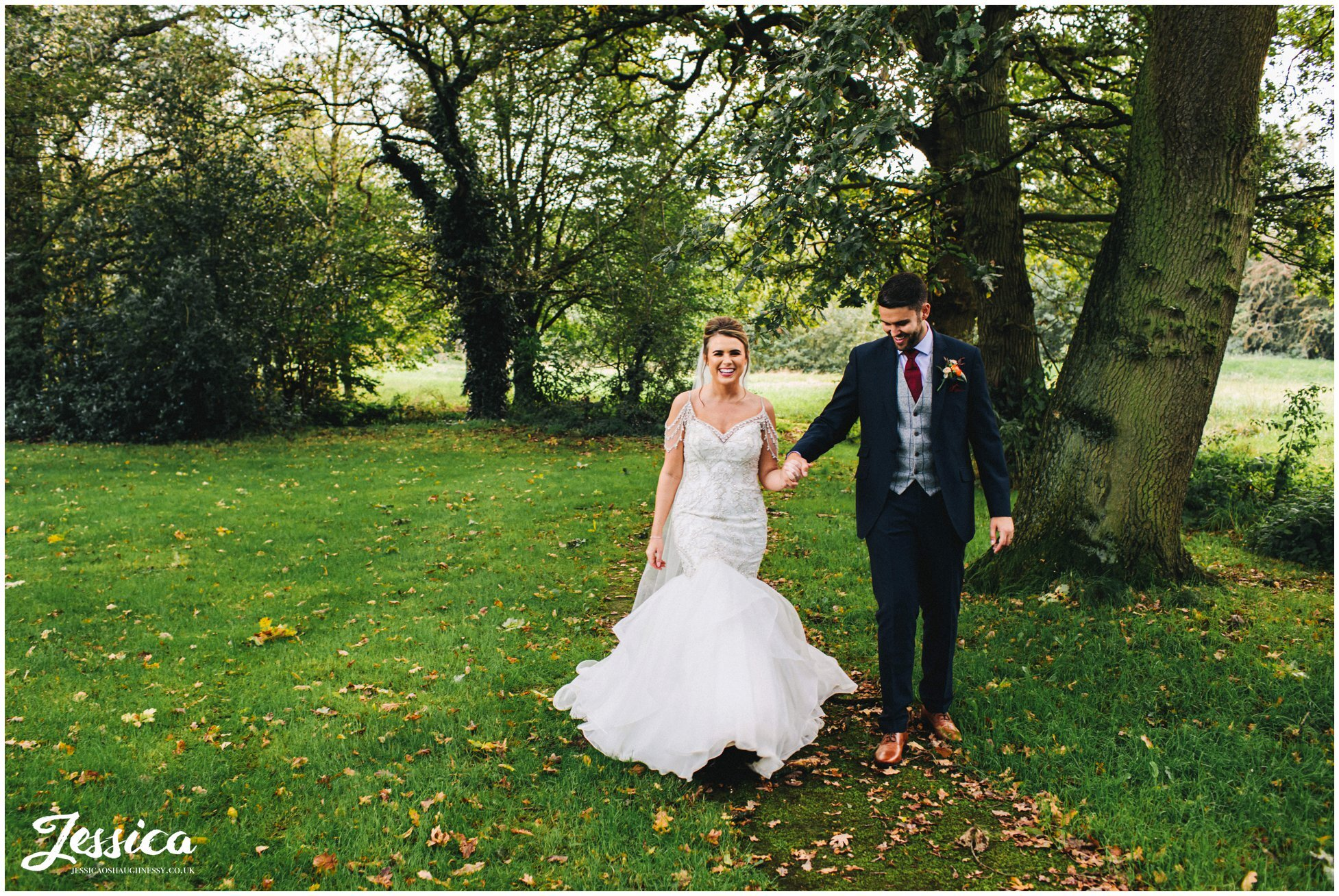 couple walk hand in hand through trees at the oak tree of peover