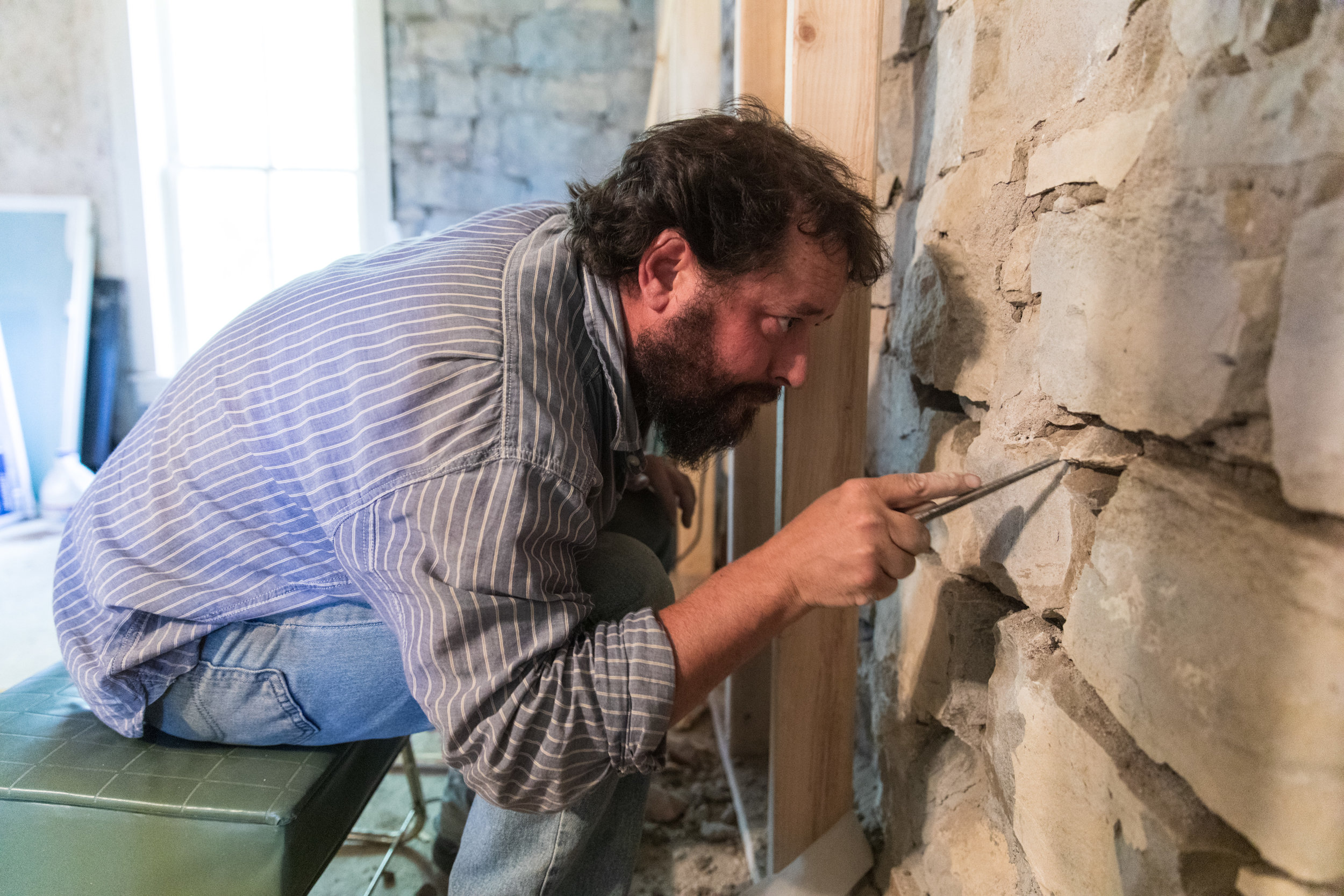 Ben Gilstrap chiseling out the mortar and dirt between stones used to build the ranch headquarters over a hundred years ago.