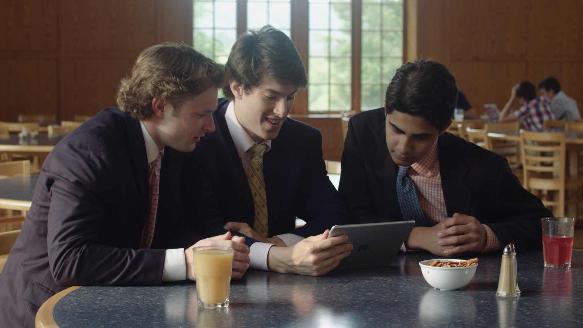 Three hockey players from TP watching game footage on an ipad. We shot this on the Ursa Mini Pro during lunch hour in the dining hall.
