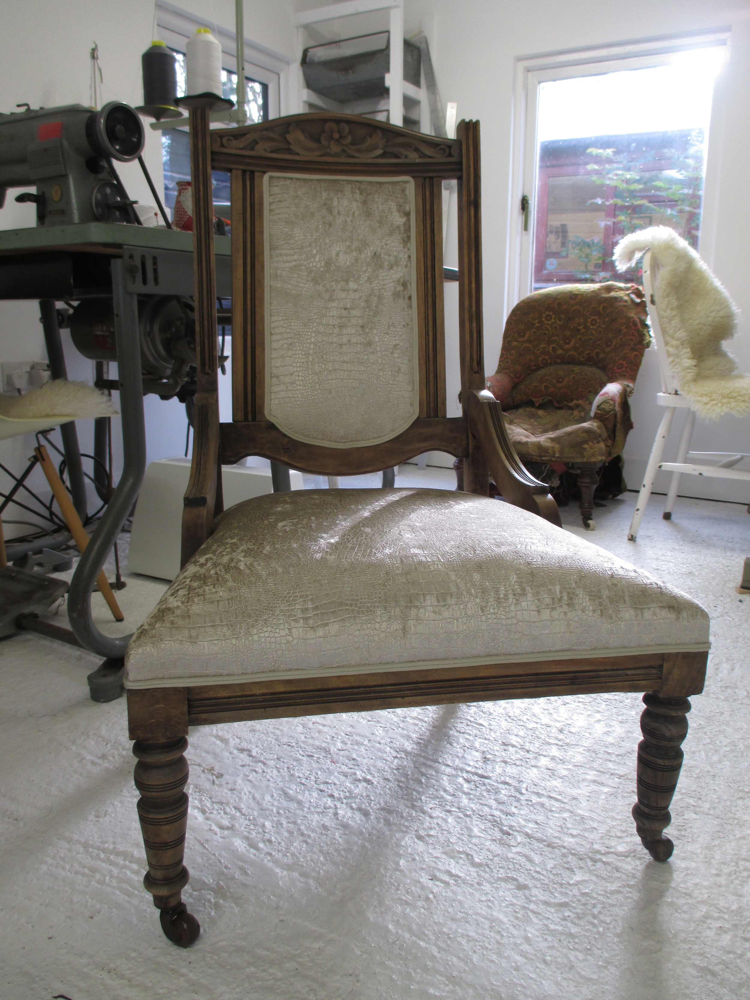 The owner of this chair had stripped it down to the frame and taken off the dark polish finish on the show wood. The shimmery fabric looks great against the freshly waxed wood.