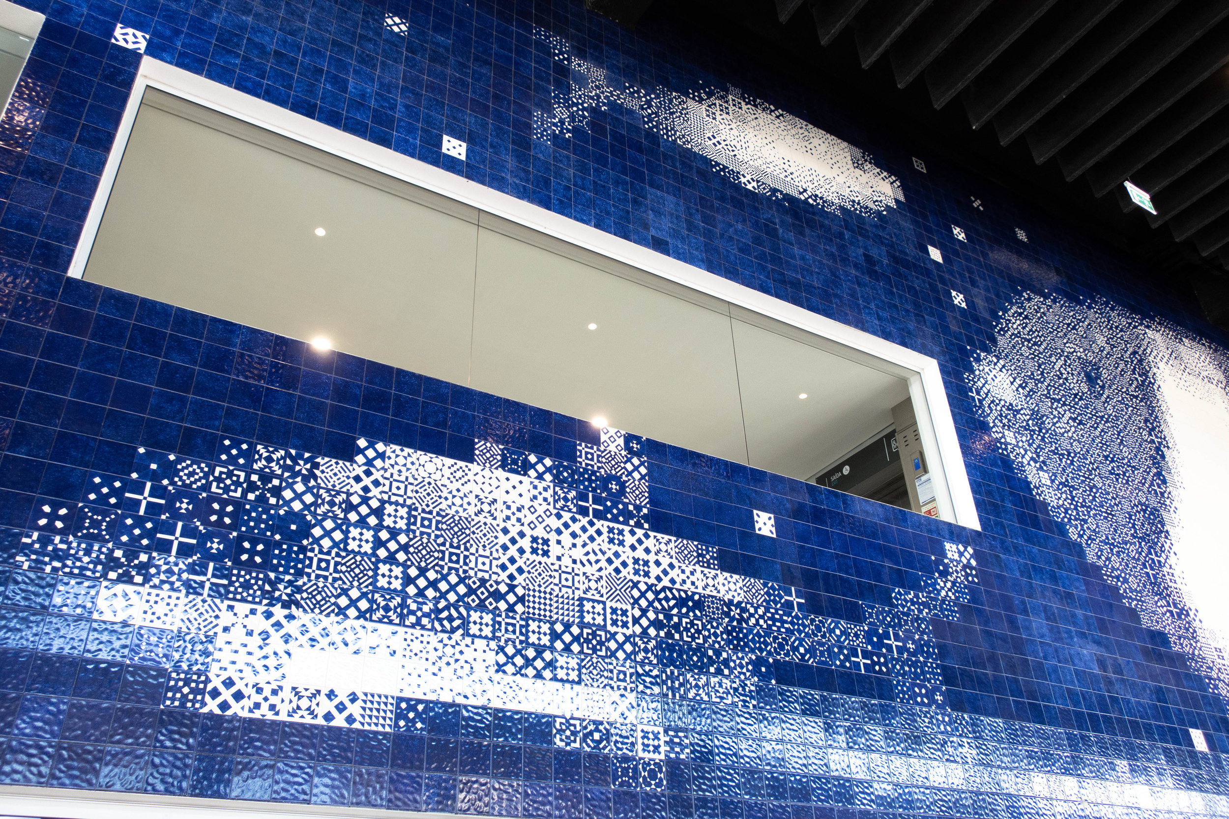 Giant pixelated marine animals are covering the wall. It shows how contemporary design (1998, but still looks modern) meets the manufactured tradition and gives it a new life. Each tile has a unique pattern to create different tones of blue.