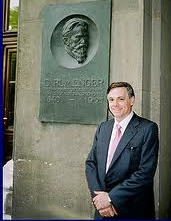 Jesús Huerta de Soto in front of a Carl Menger memorial plaque