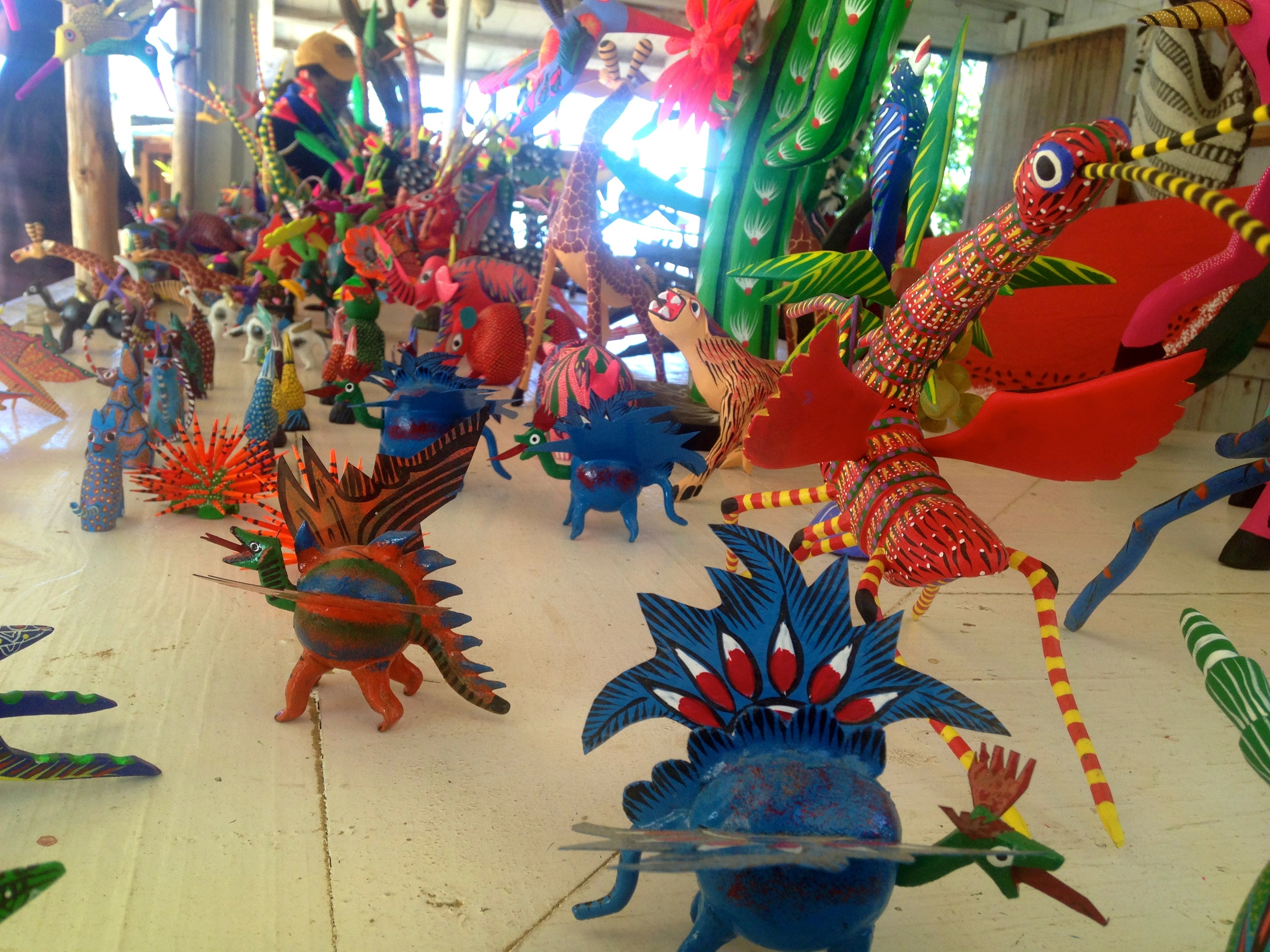 Alebrijes, or brightly colored folk art sculptures made from wood found in the mountains. One artist said that the shape of the wood determines the creatures he produces.