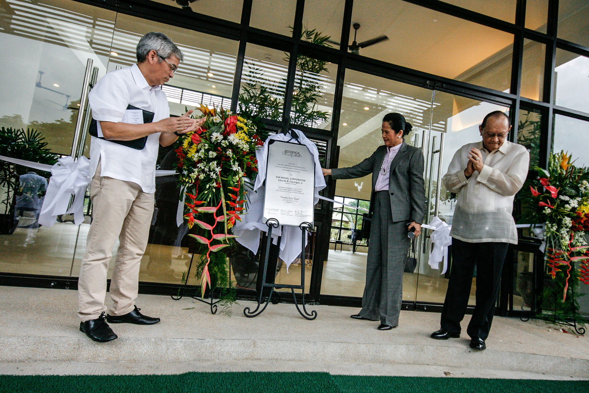 """Mr. Eduardo """"Danding"""" Congjuangco (right) and his wife,Soledad """"Gretchen"""" Cojuangco (center), unveil a commemorative marker in their honor whileBr. Edmundo Fernandez FSC, LEAD Visitor, looks on."""