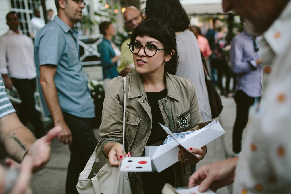 Melody Santiago Cummings hands out unofficial Poetry Society of America bicycle spoke cards.