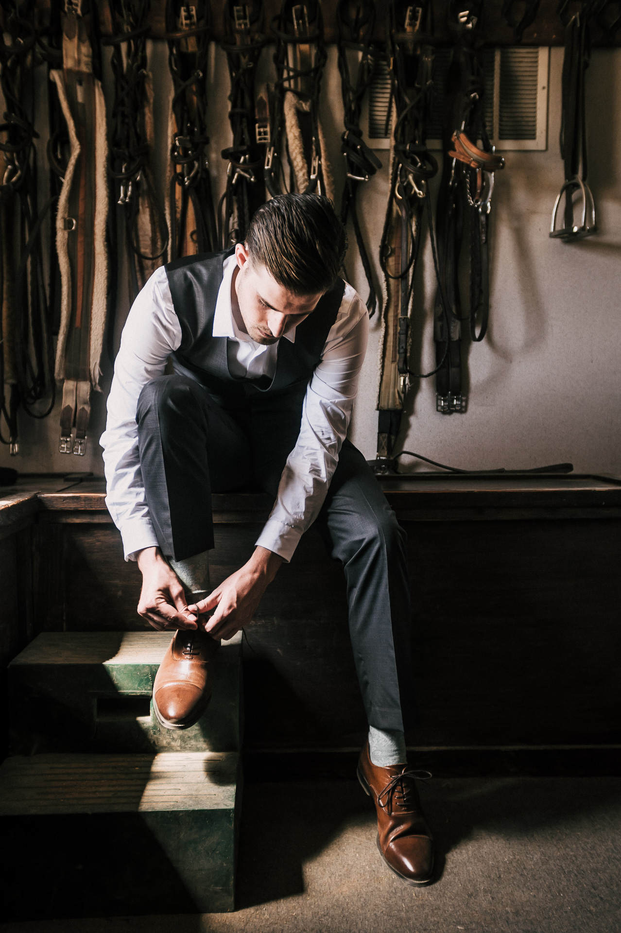 Groom sits to lace his shoes while getting ready in the rustic saddle room at Quail Haven Farm.