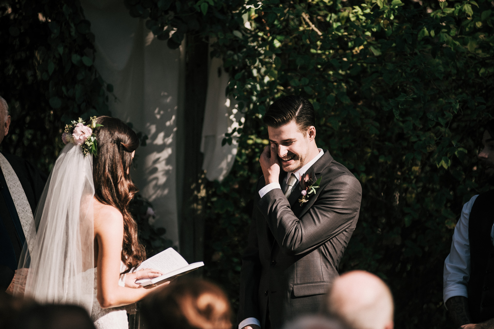 Photographer captures groom tearing up as his soon to be wife reads her vows during their marriage ceremony at Quail Haven Farm.