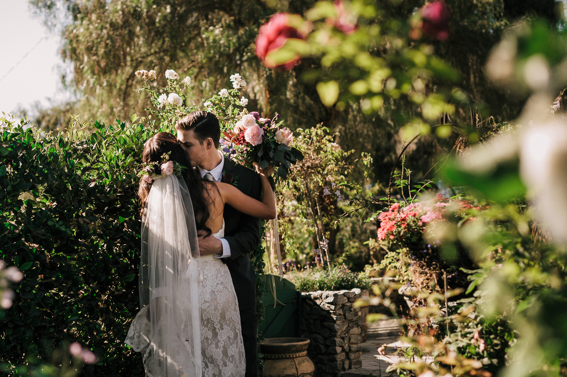 Newly married couple kisses in the gardens of the rustic Quail Haven Farm.