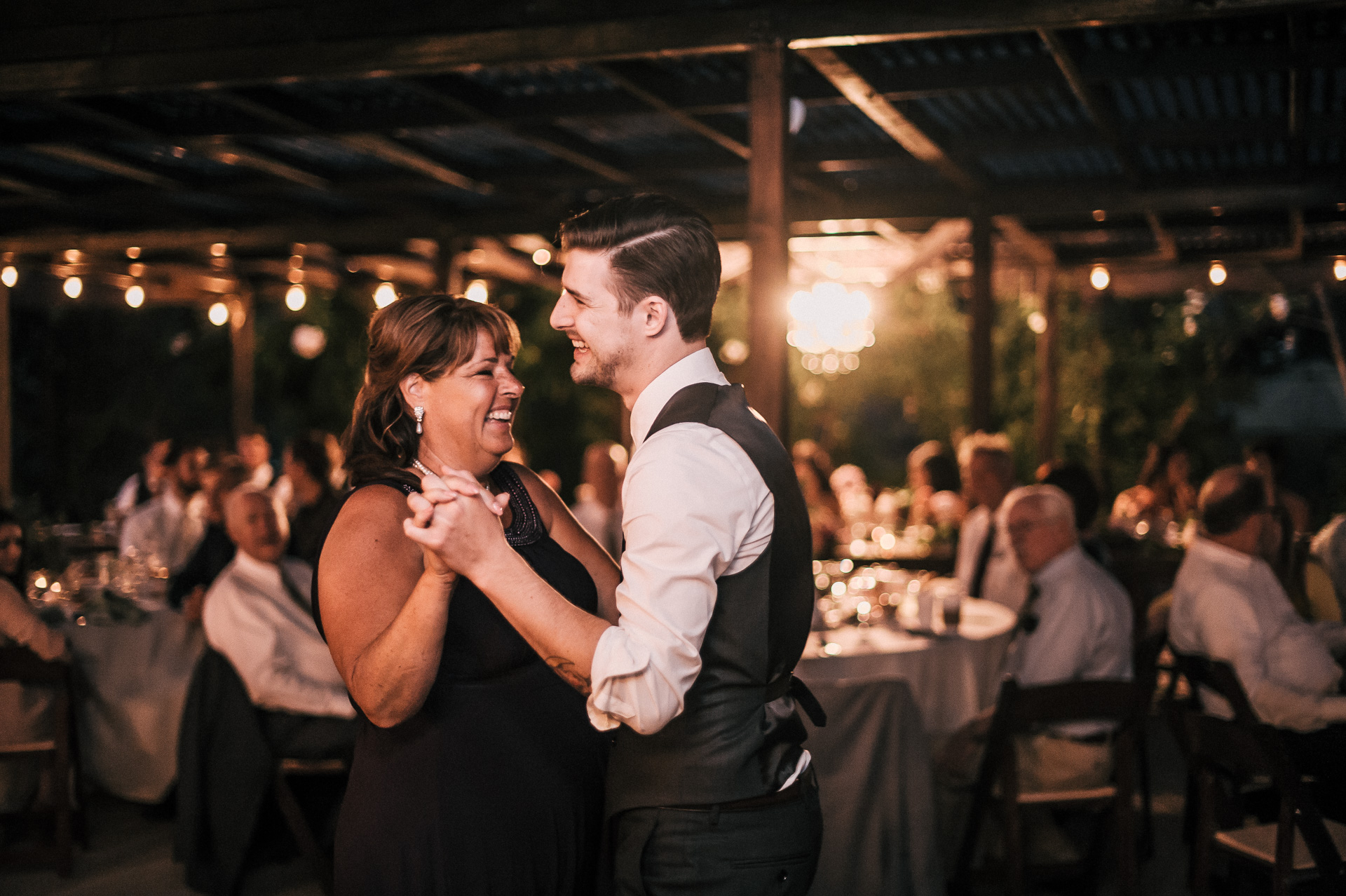 Groom dances with his mother and shares a laugh at his Quail Haven Farm wedding reception.